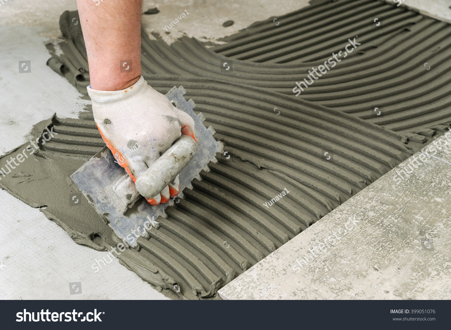 Laying ceramic tiles troweling mortar onto stock photo 399051076 laying ceramic tiles troweling mortar onto a concrete floor in preparation for laying floor tile dailygadgetfo Choice Image