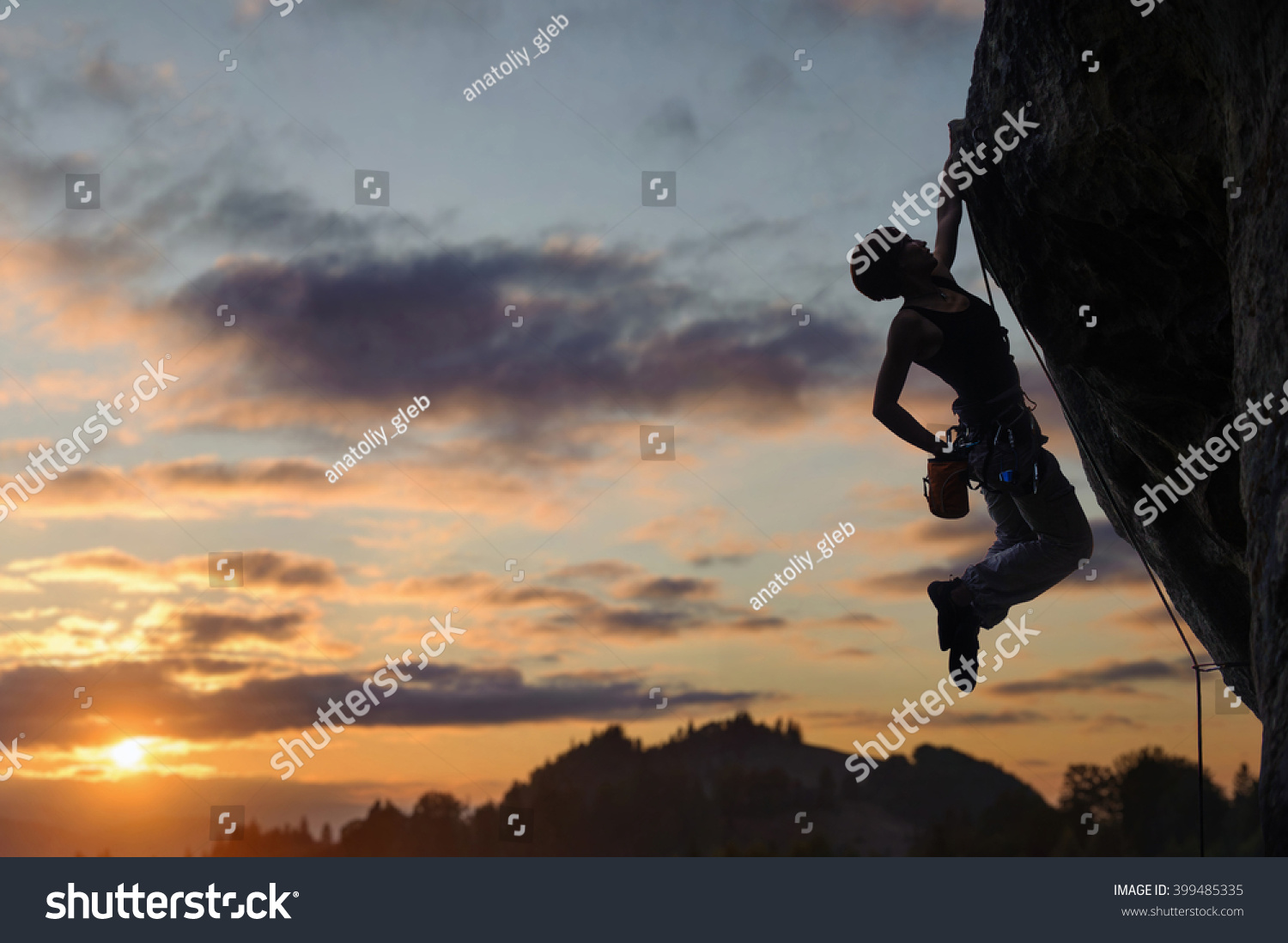 Silhouette of athletic female rock climber climbing steep rock wall against amazing sunset sky in the mountains Girl is hanging on one hand and holding hand in magnesium bag