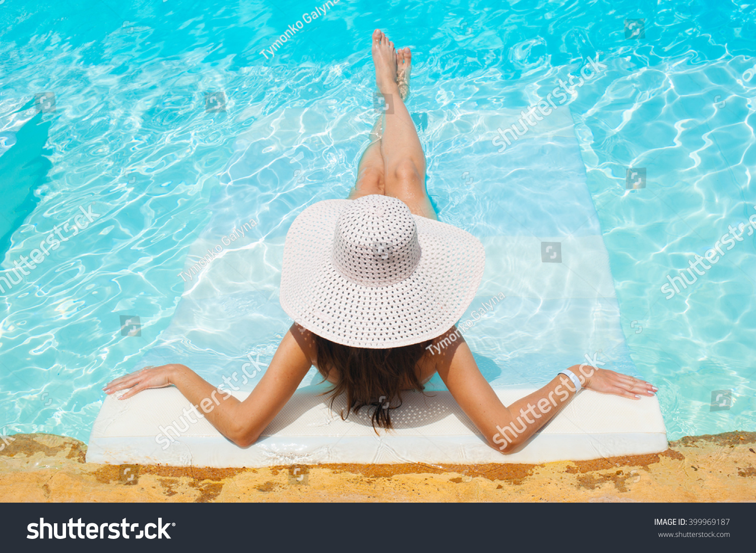 beautiful woman white hat and bikini lying in a pool