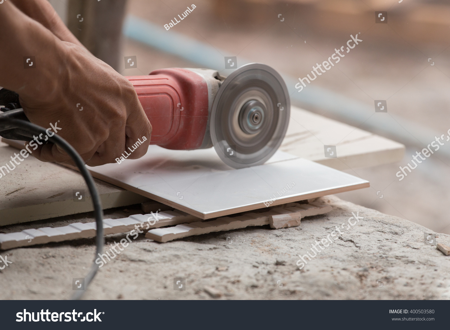 Worker cutting tile using angle grinder stock photo 400503580 worker cutting a tile using an angle grinder at construction site dailygadgetfo Images