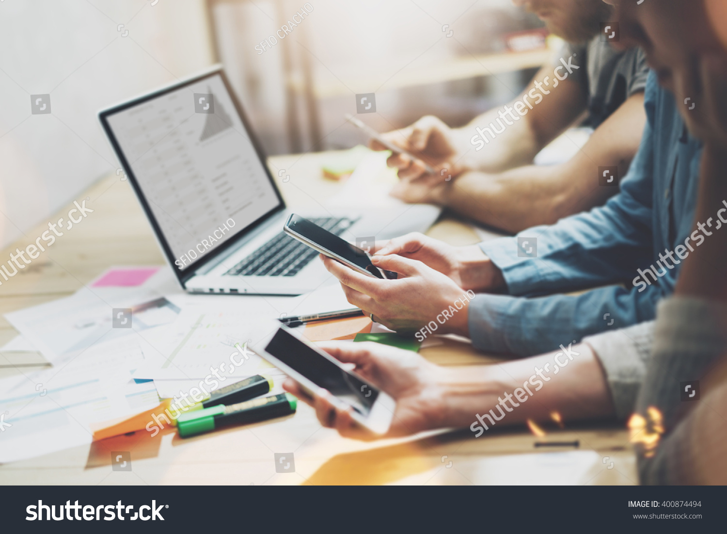 Digital world. Photo young business managers crew working with new startup project.Notebook on wood table. Using modern smartphones, typing message, analyze plans screen. Horizontal, film effect. #400874494