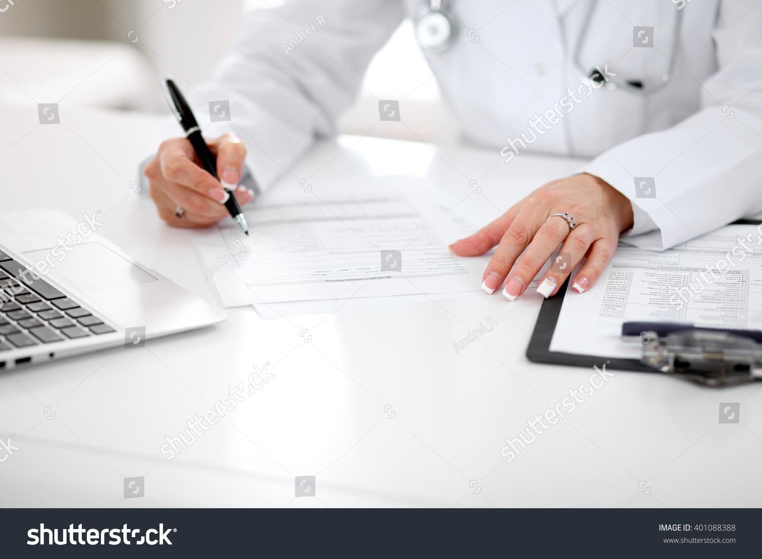royalty close up of a female doctor filling  close up of a female doctor filling out application form sitting at the table
