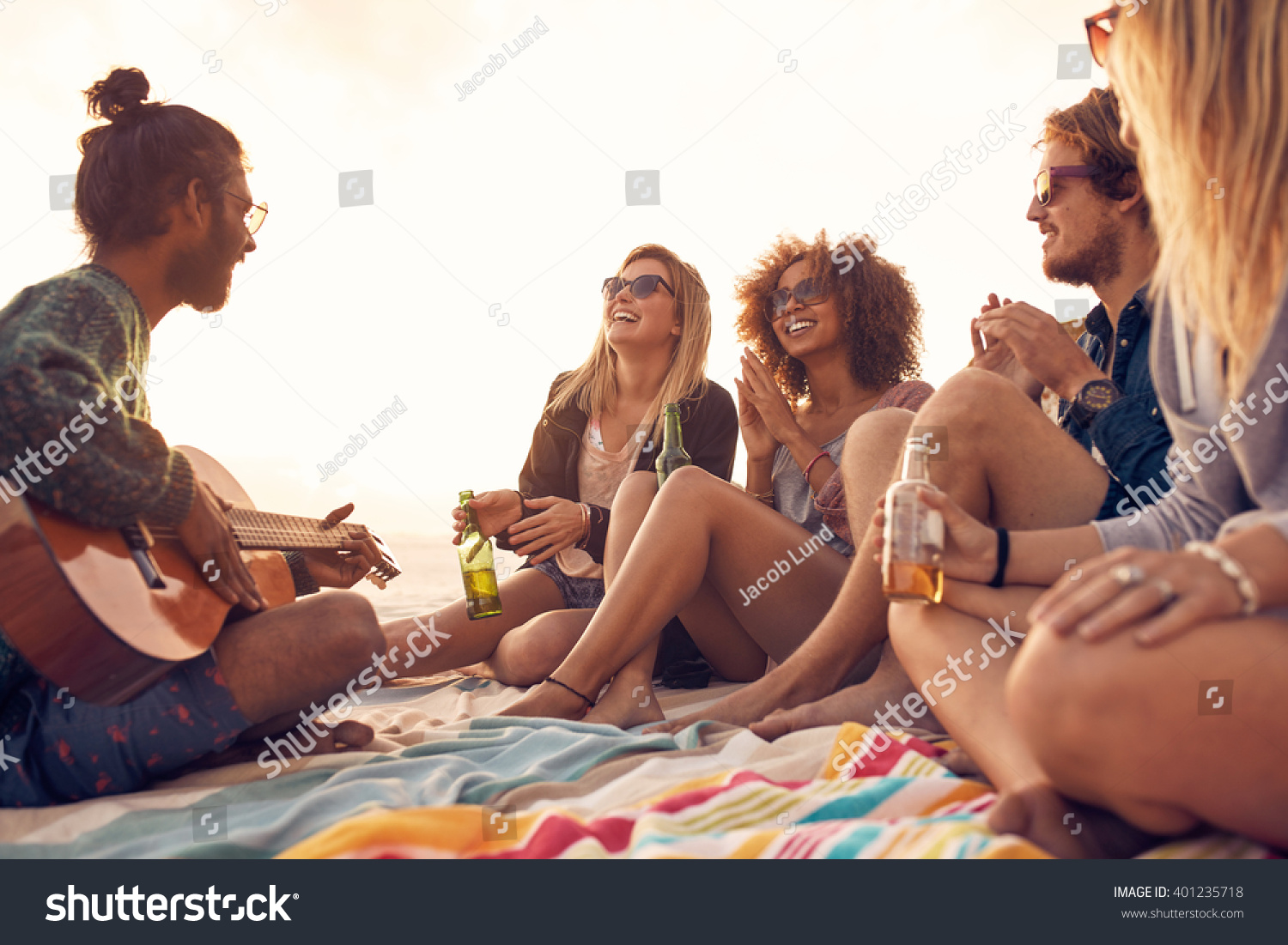 Happy hipsters relaxing and playing guitar at the beach Friends drinking beers and listening to music Having fun at beach party in evening