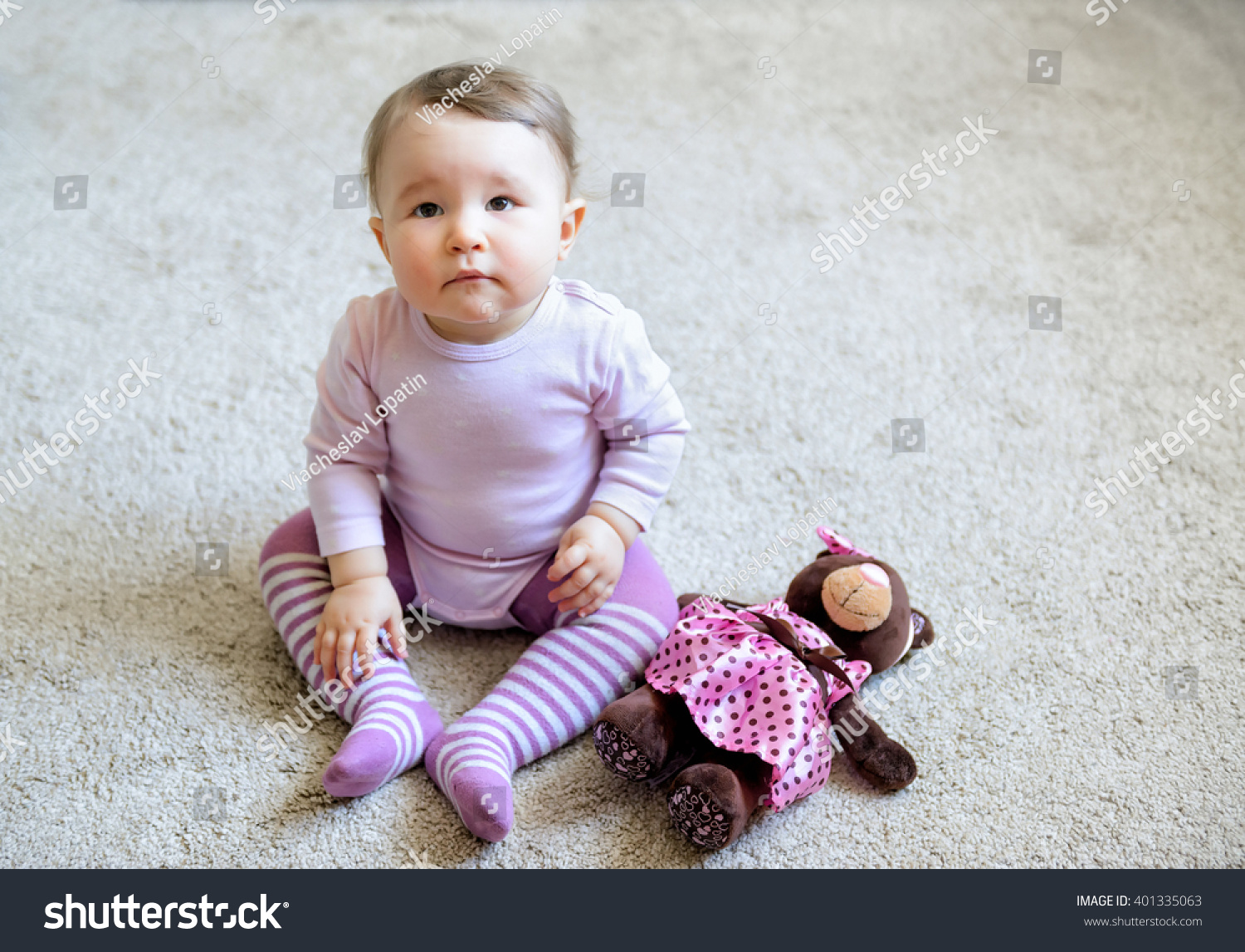 thoughtful serious nice baby girl sitting stock photo (edit now