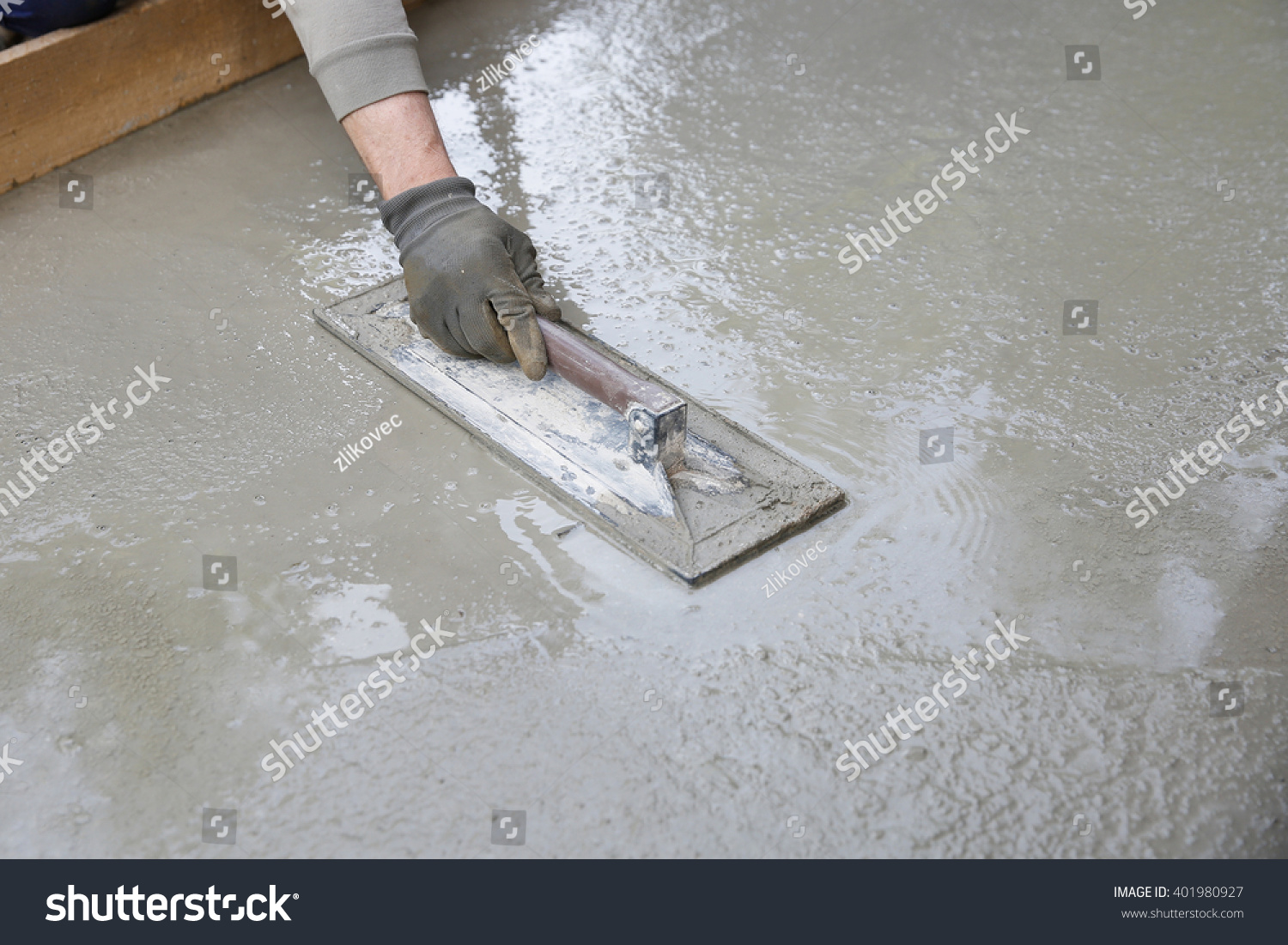 Mason Leveling And Screeding Concrete Floor Base With Square Trowel In  Front Of The House.