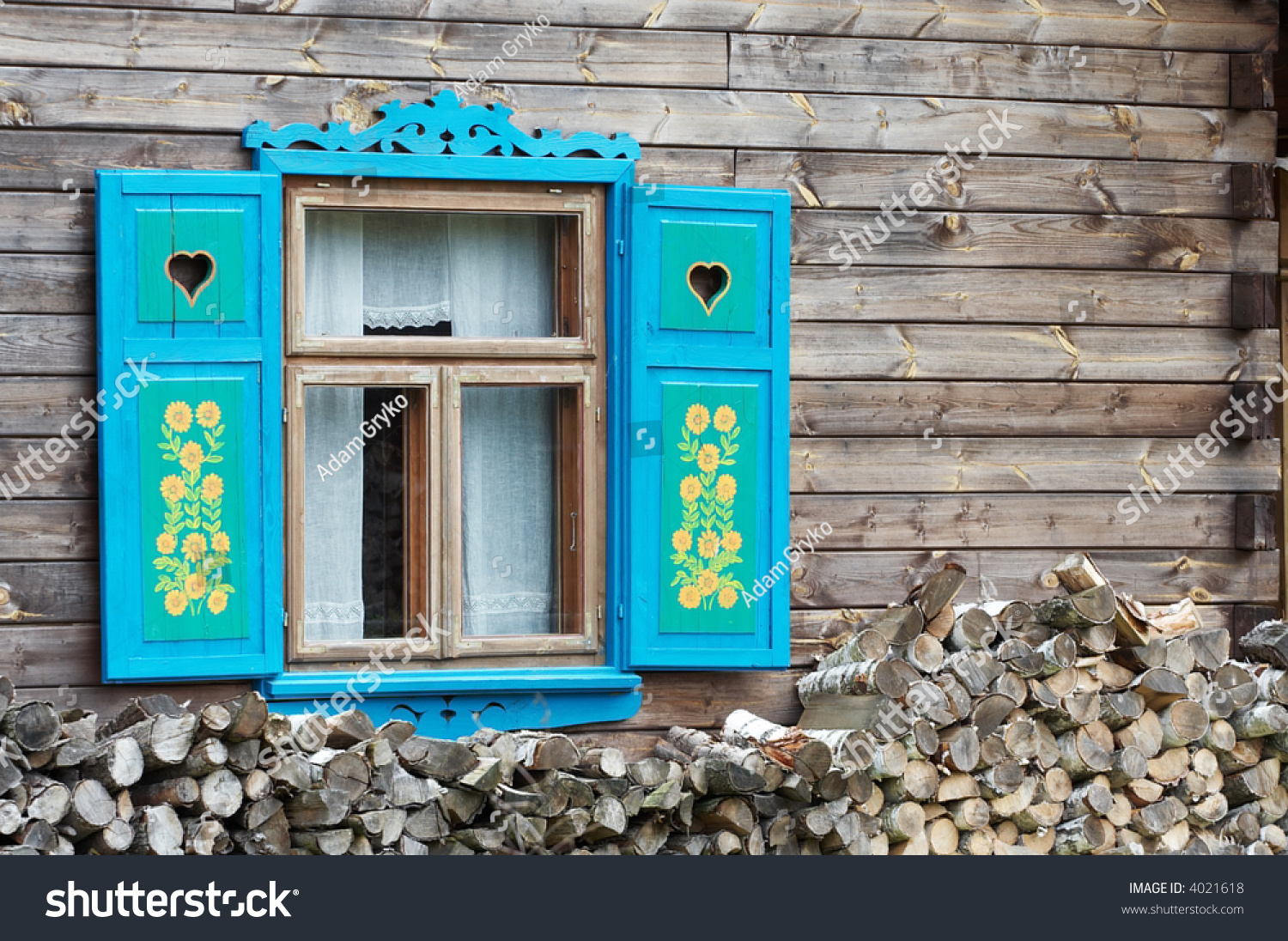 opened window with decorative colorful shutters and logs below - Decorative Shutters
