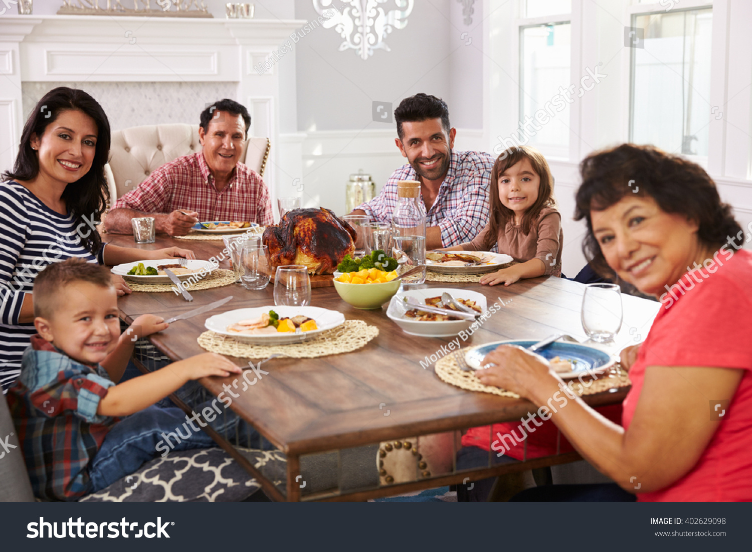 Extended Hispanic Family Enjoying Meal At Table
