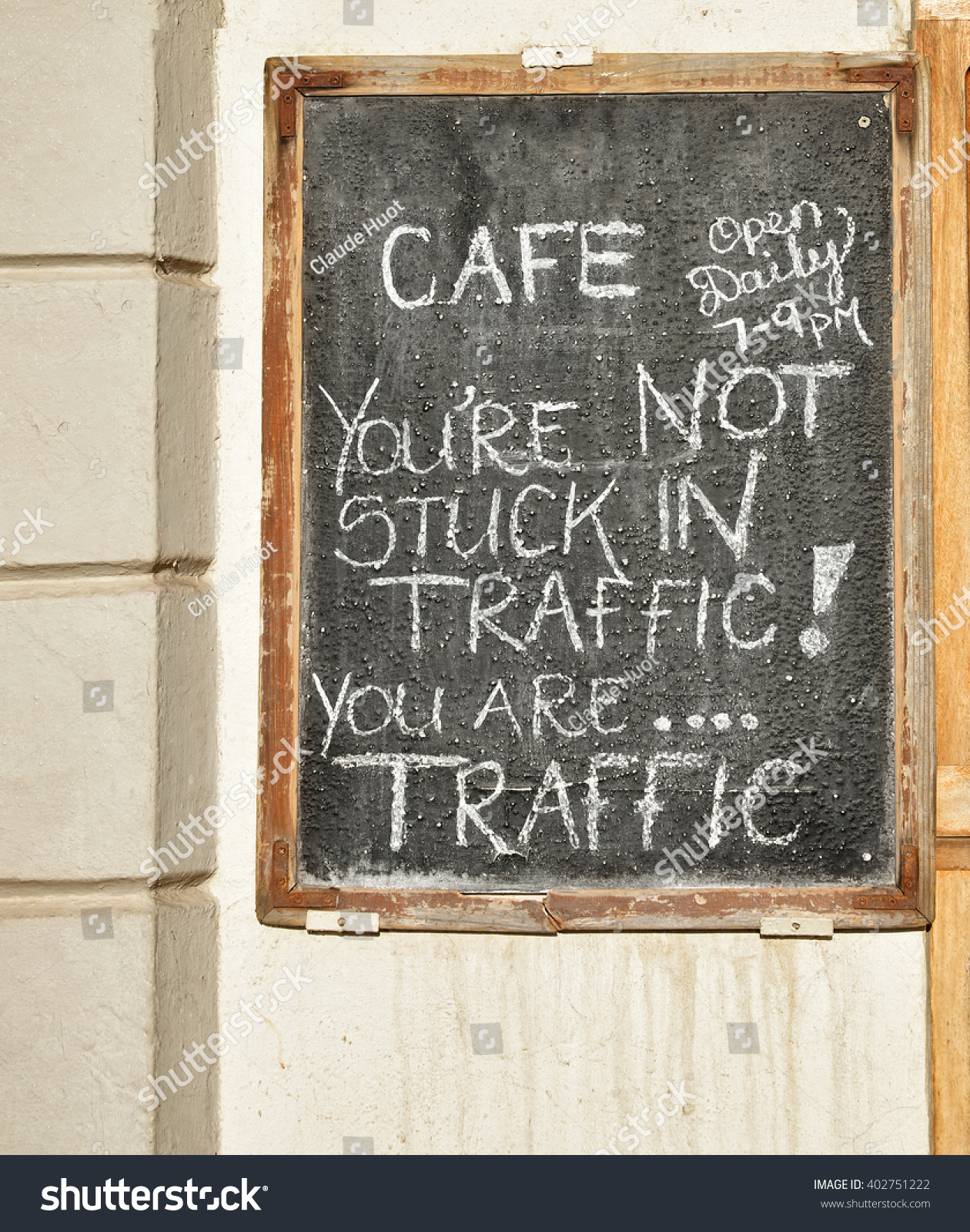 Humorous sign posted in front of a cafe on a busy street