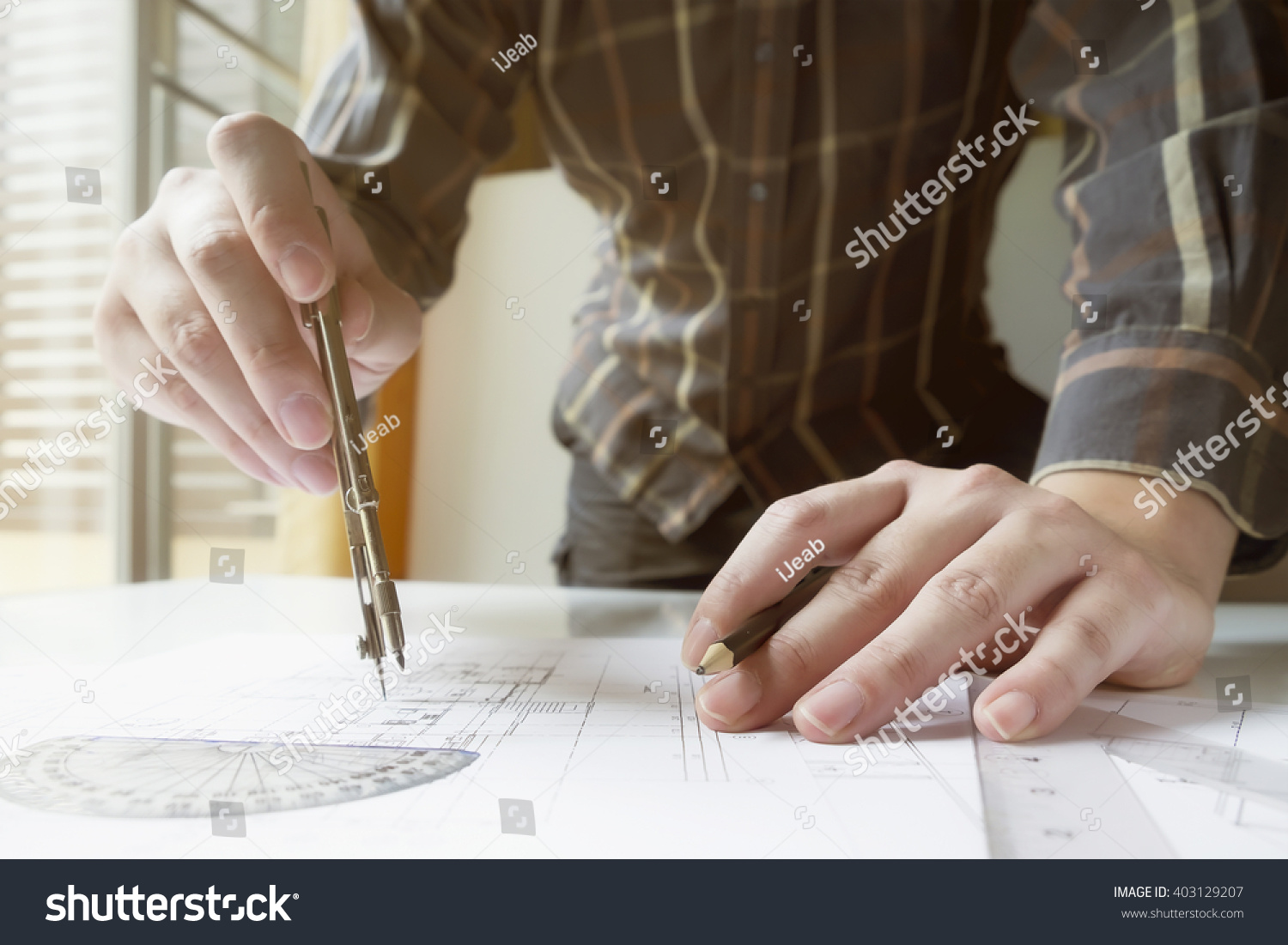 Man's hand with a compass Mechanical engineer at work Technical drawings Pencil compass calculator and hand man Paper with technical drawings and diagrams User sunlight vintage retro filter