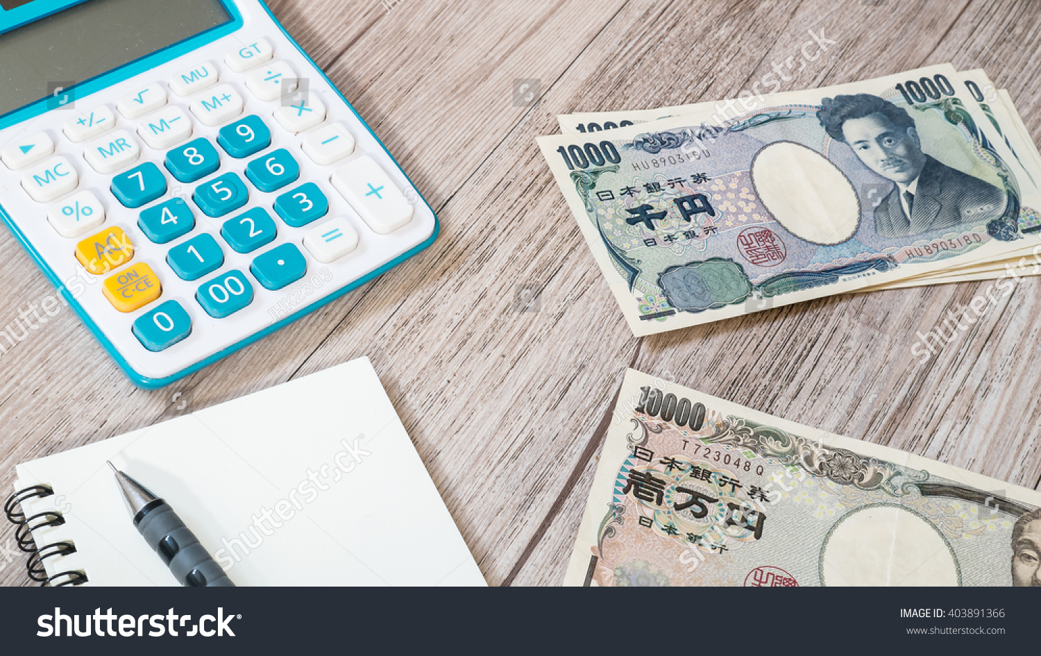 Japan money japanese yen currency and calculator notebook pencil on wooden background