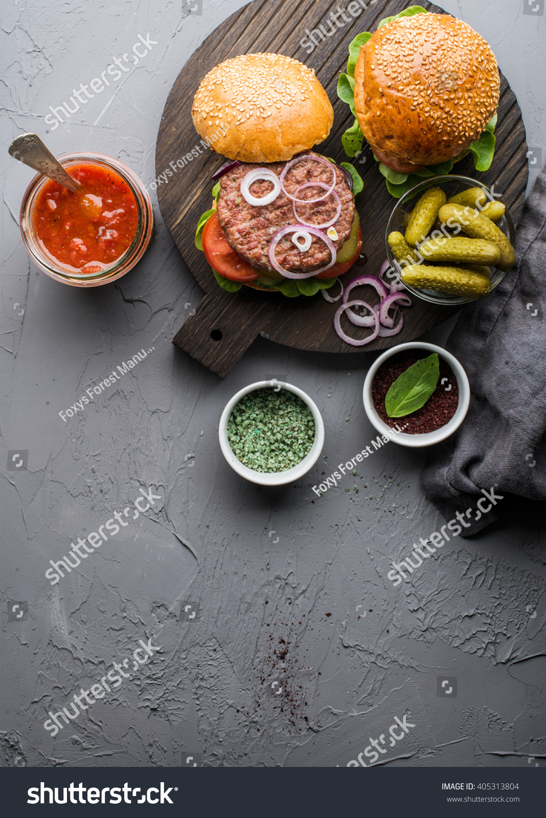 Fresh homemade burgers on dark serving board with spicy tomato sauce green salt pepper pickles and onion over concrete textured background Top view copy space