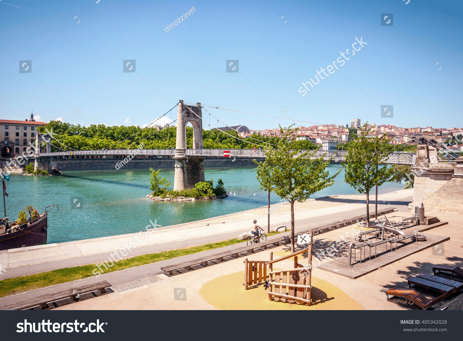 View on sunlit bridge over calm river in Lyon, France