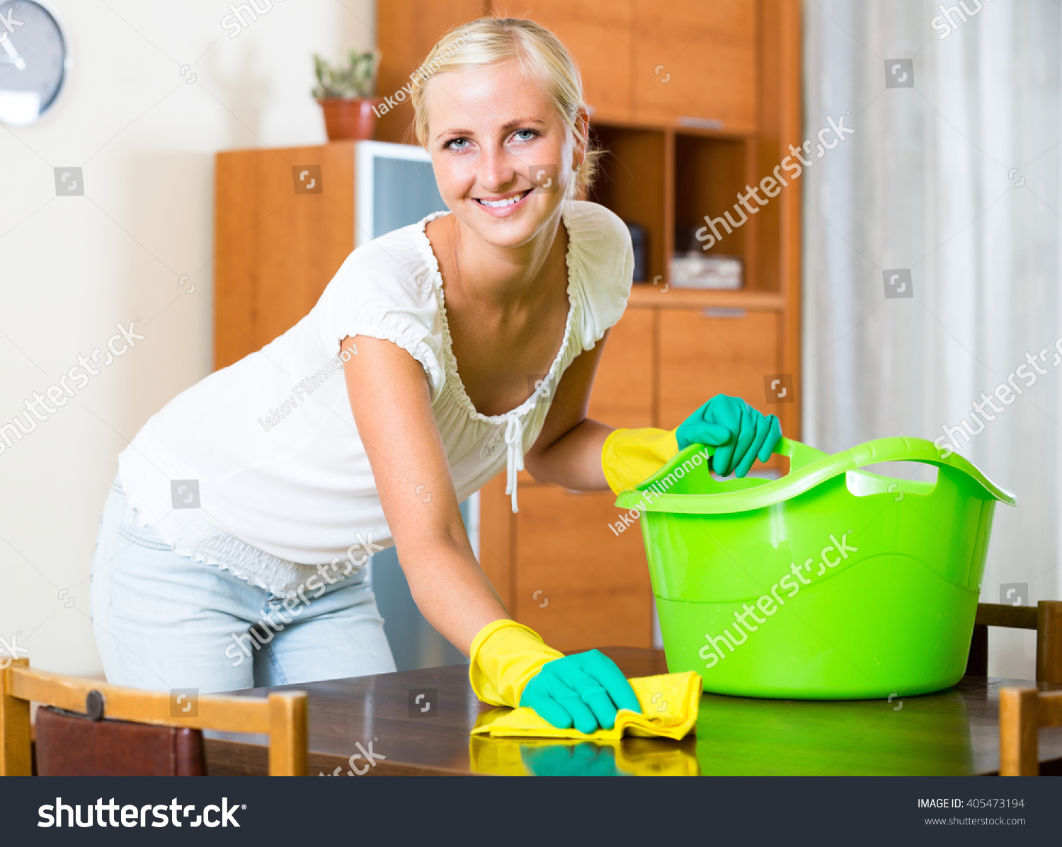 dusting furniture. Cheerful Young Housewife In Rubber Gloves Dusting Furniture At Home