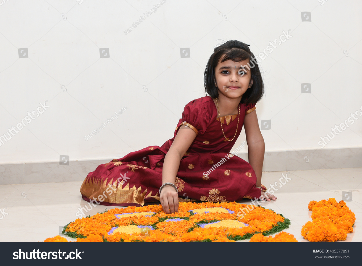 14a4c87bf Happy smiling playful young Indian / South Indian girl wearing traditional  dress holding / making flower