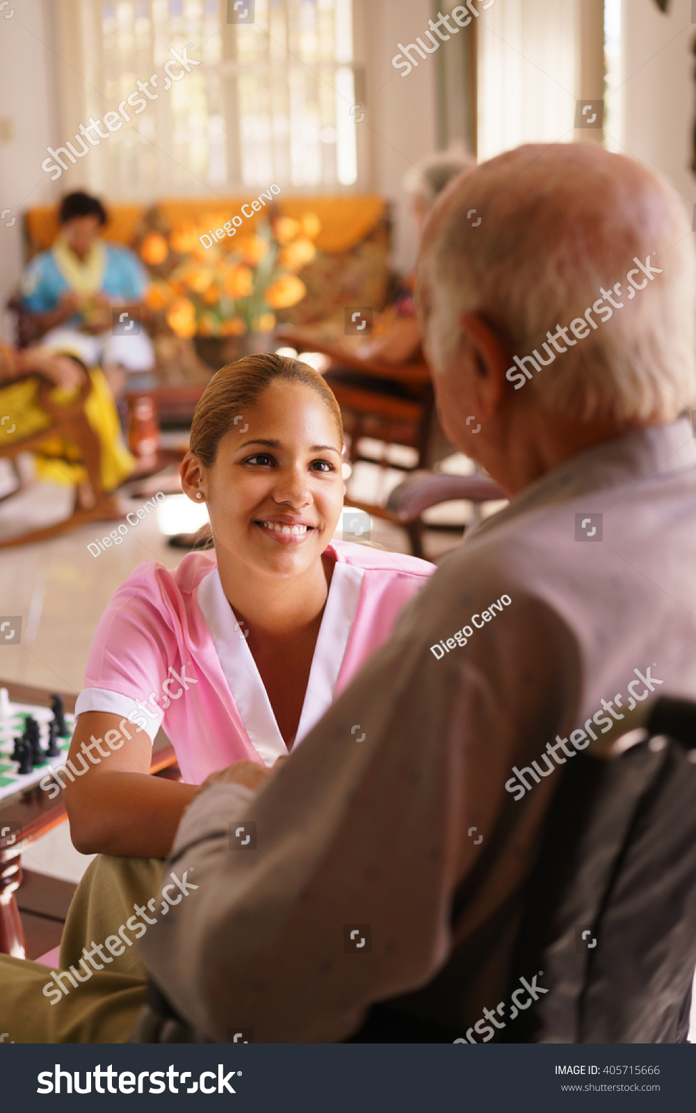 old people in geriatric hospice young attractive hispanic woman working as nurse takes care of. Black Bedroom Furniture Sets. Home Design Ideas
