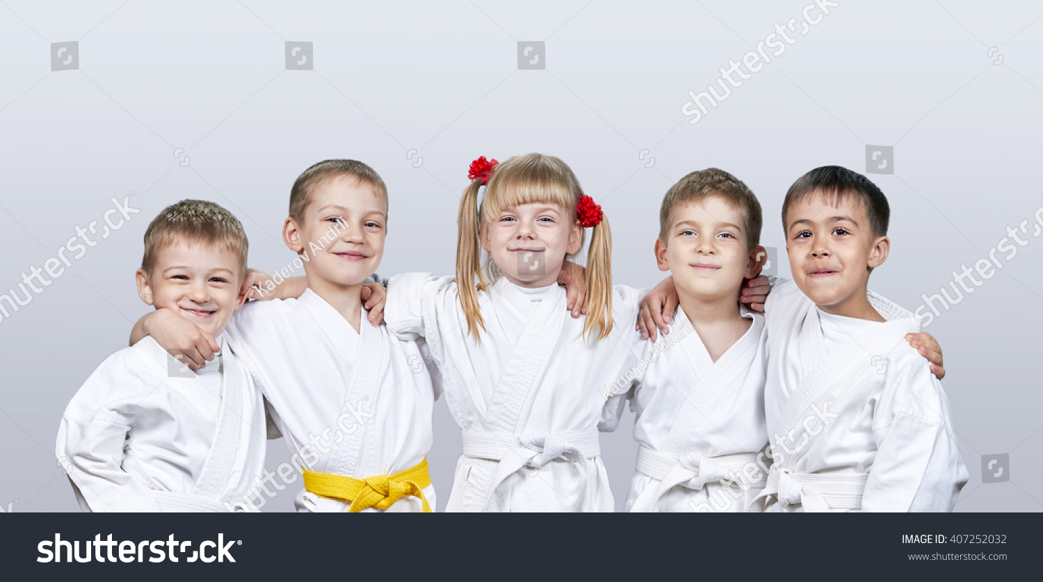 Cheerful children in karategi on a gray background #407252032