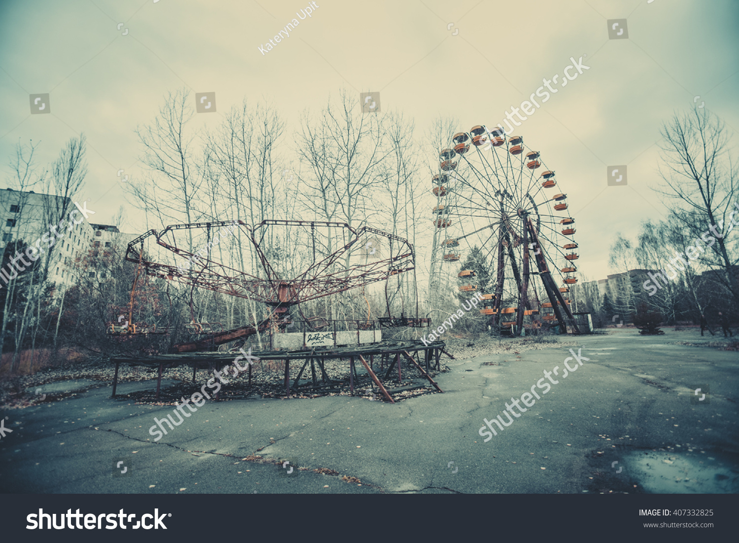 Abandoned carousel and abandoned ferris  at an amusement park in the center of the city of Pripyat, the Chernobyl disaster, the exclusion zone, a ghost town #407332825