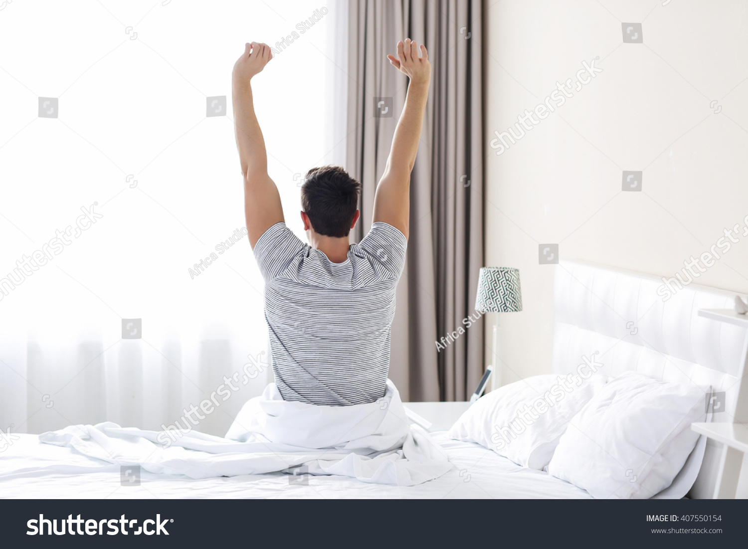 A young man waking up in bed and stretching his arms