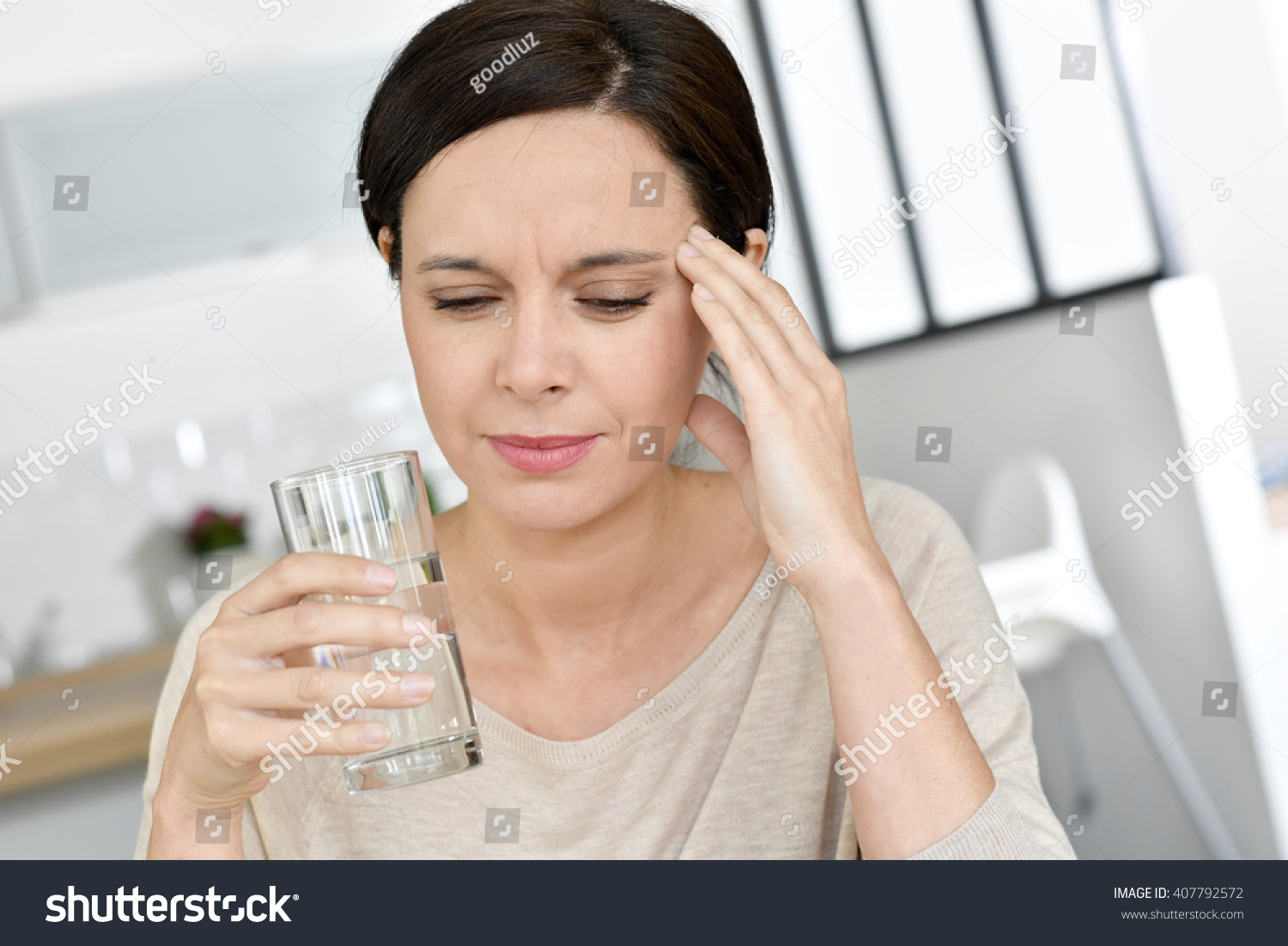 Mature woman having migraine drinking water