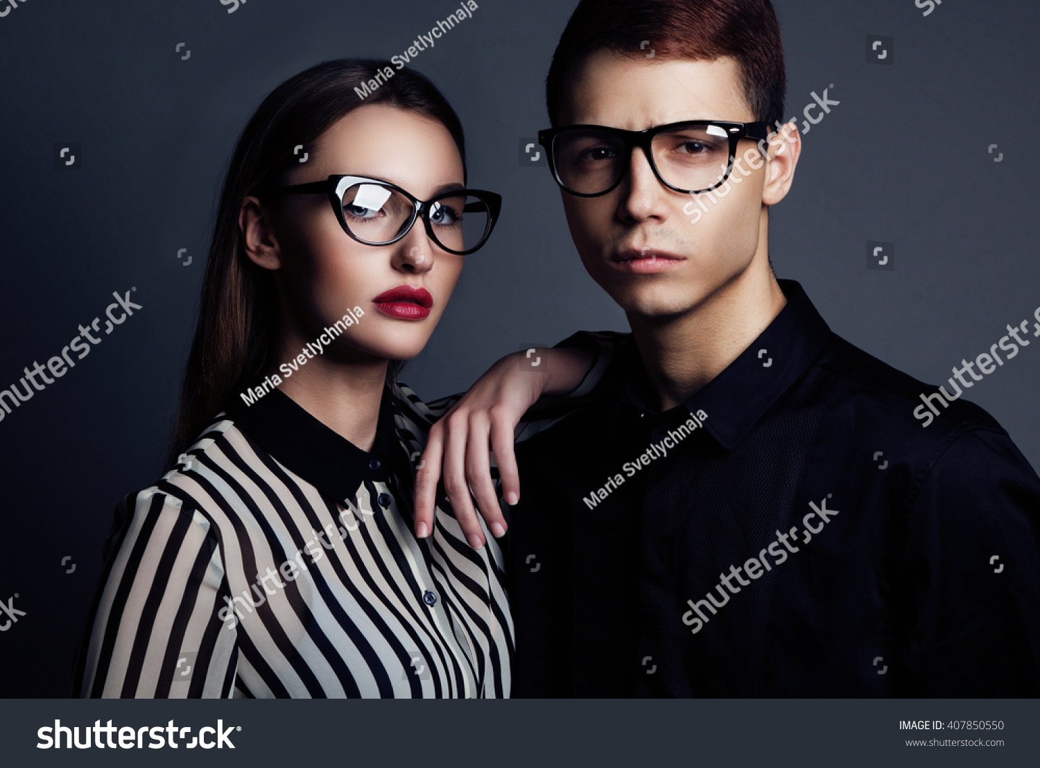 01865f74a4e Fashion models couple wearing sunglasses. Sexy woman and handsome young man portrait  over dark background