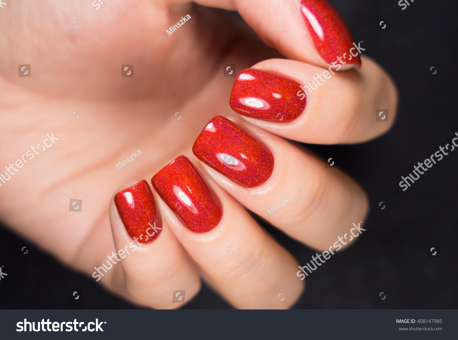 Woman with beautiful manicured red fingernails gracefully crossing her hands to display them to the viewer on a white background in a fashion glamour and beauty concept