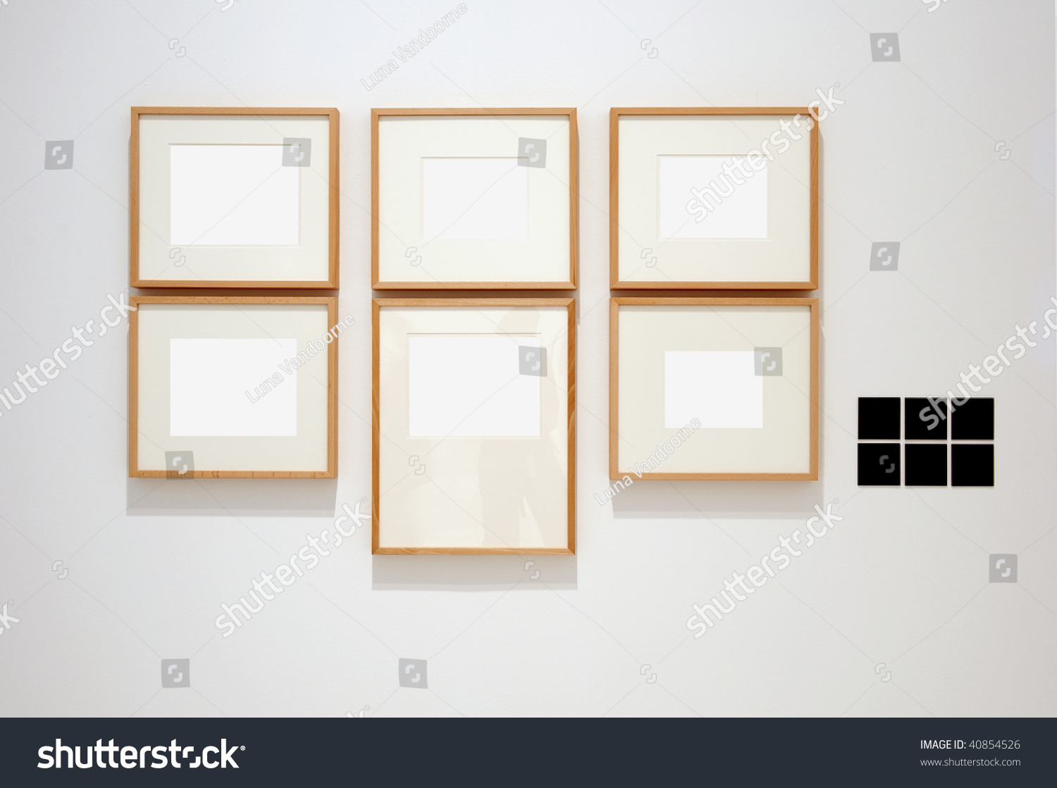 six empty frames on white wall in museum with labels - Empty Frames On Wall
