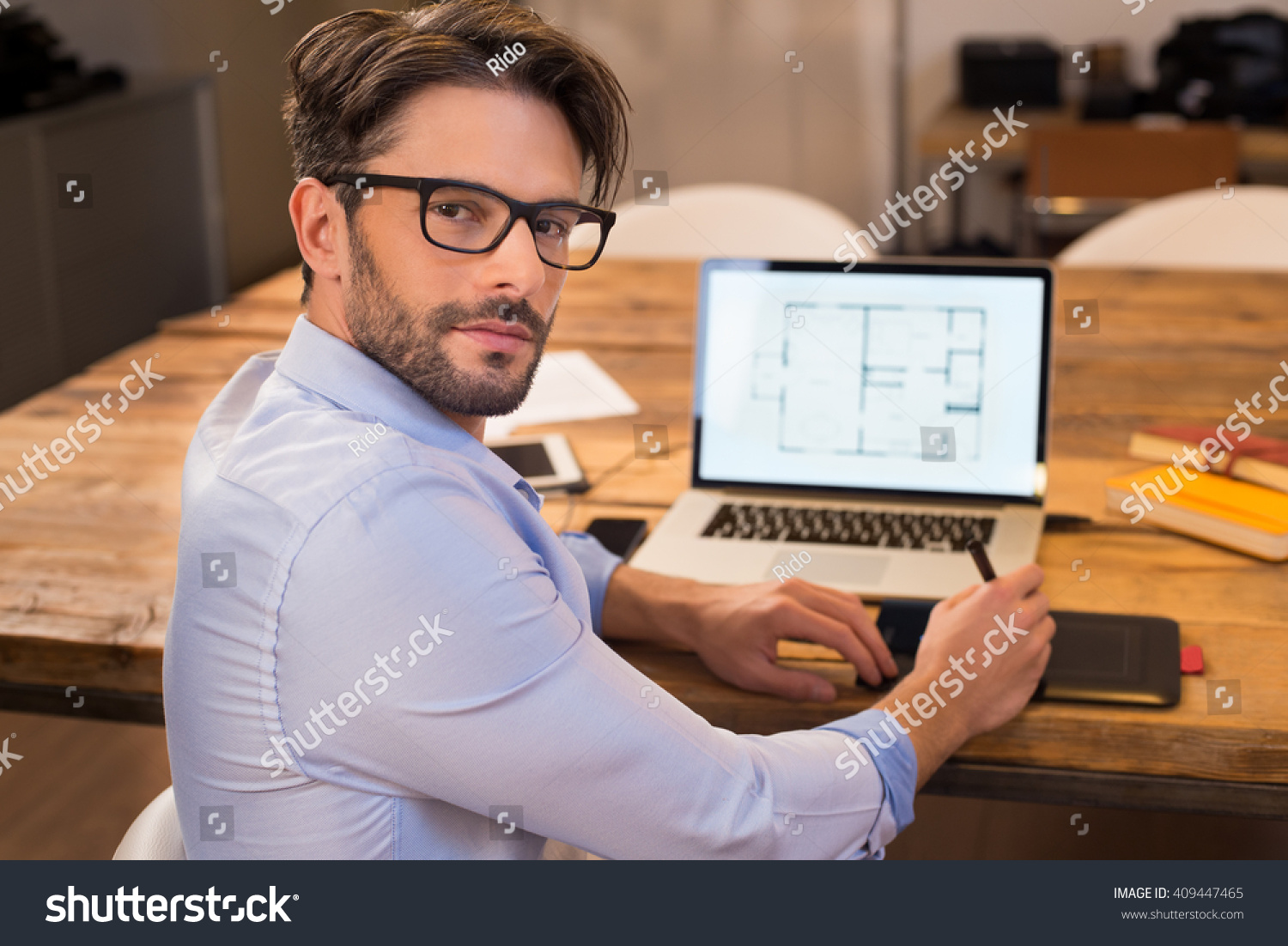 Portrait Of A Young Interior Designer Working At Office. Man Working On  Laptop Turning Around