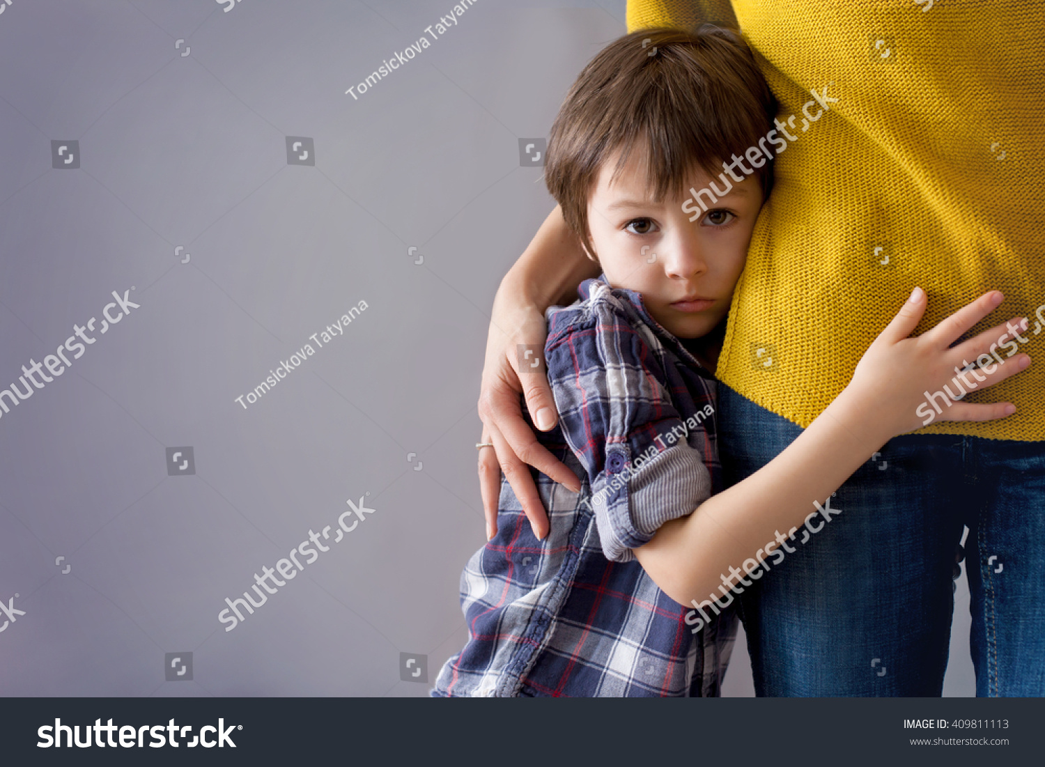Sad little child, boy, hugging his mother at home, isolated image, copy space. Family concept #409811113