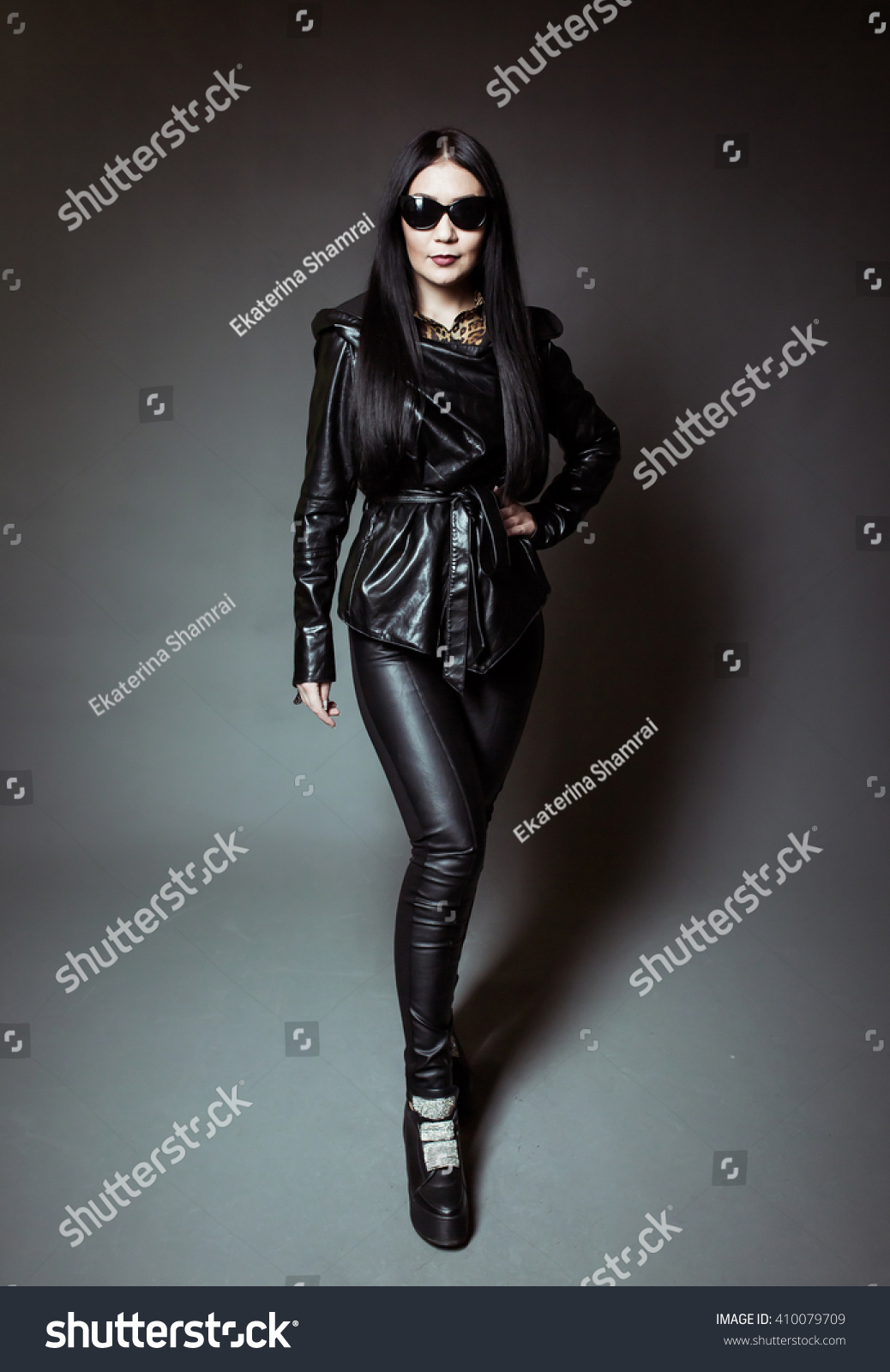 6815d4e86 Girl with black glasses in a leather jacket and leather pants on a dark  background. Royalty Free Stock ...