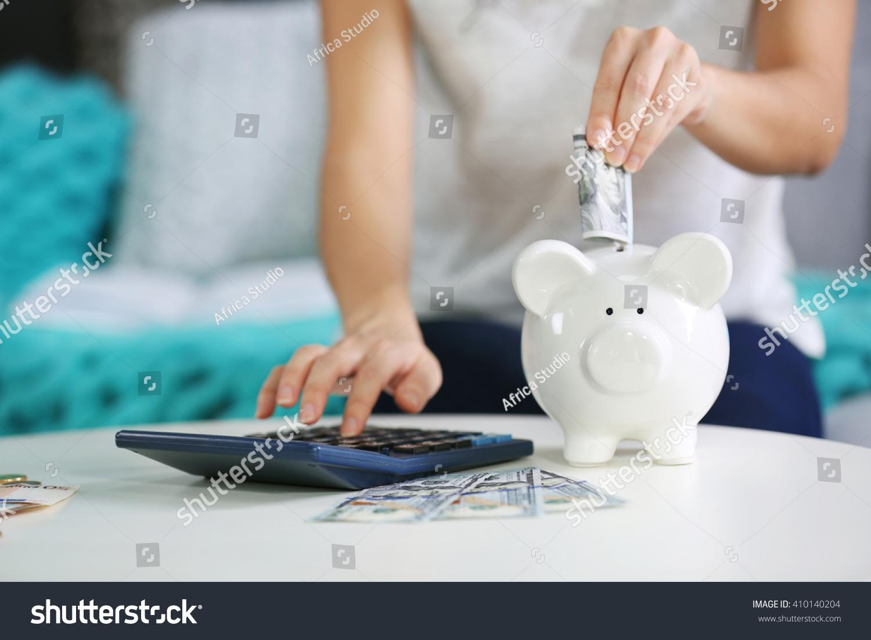 female hand putting money into piggy stock photo 410140204