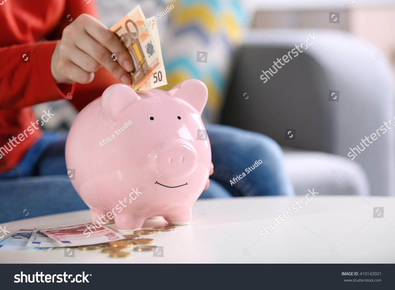 female hand putting money into piggy stock photo 410143501