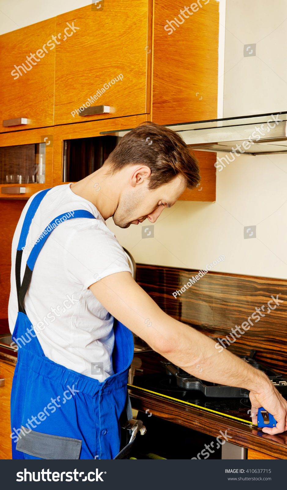 young repair man measuring kitchen cabinet stock photo 410637715