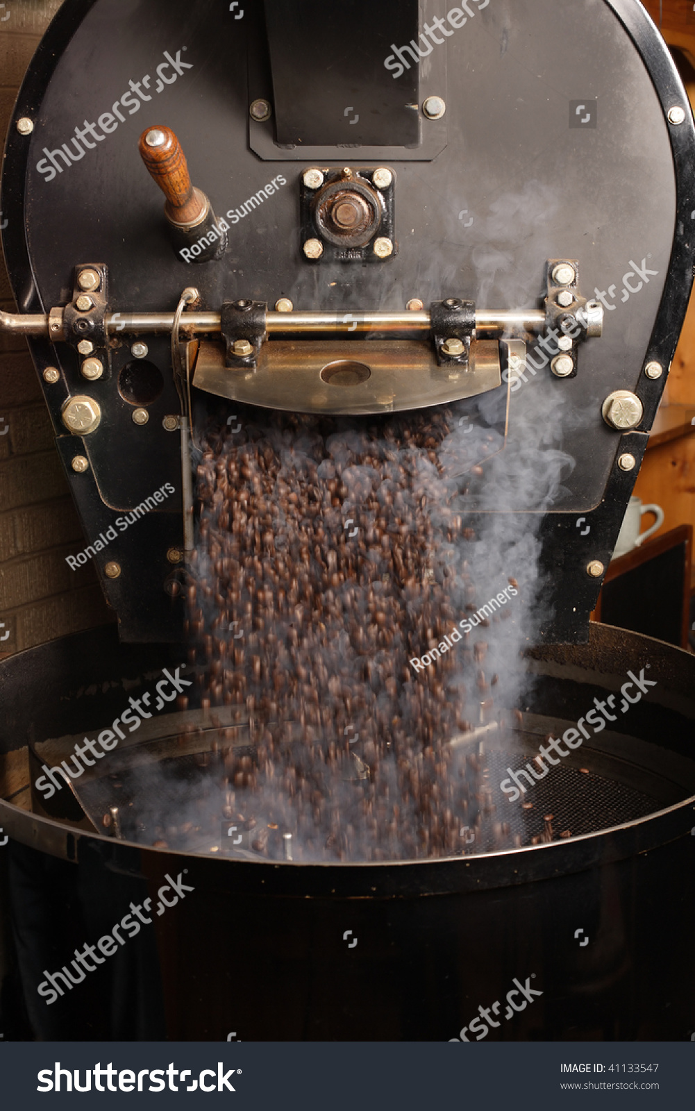 The freshly roasted coffee beans from a large coffee roaster being poured into the cooling cylinder.  Motion blur on the beans. #41133547