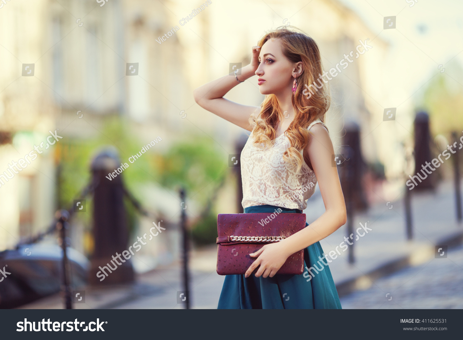 Outdoor portrait of a young beautiful fashionable lady walking posing on a street of the old city Model wearing stylish clothes Girl looking aside Female fashion concept City lifestyle