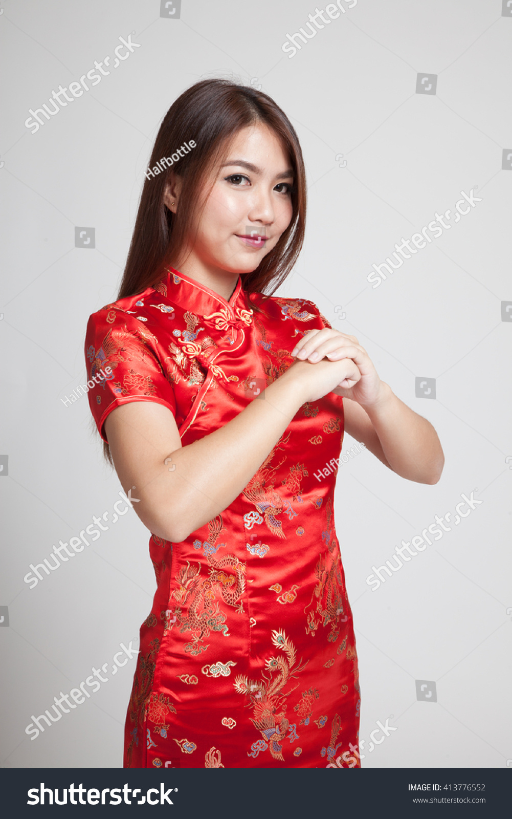 60d1aa558e Asian girl in chinese cheongsam dress with gesture of congratulation on gray  background
