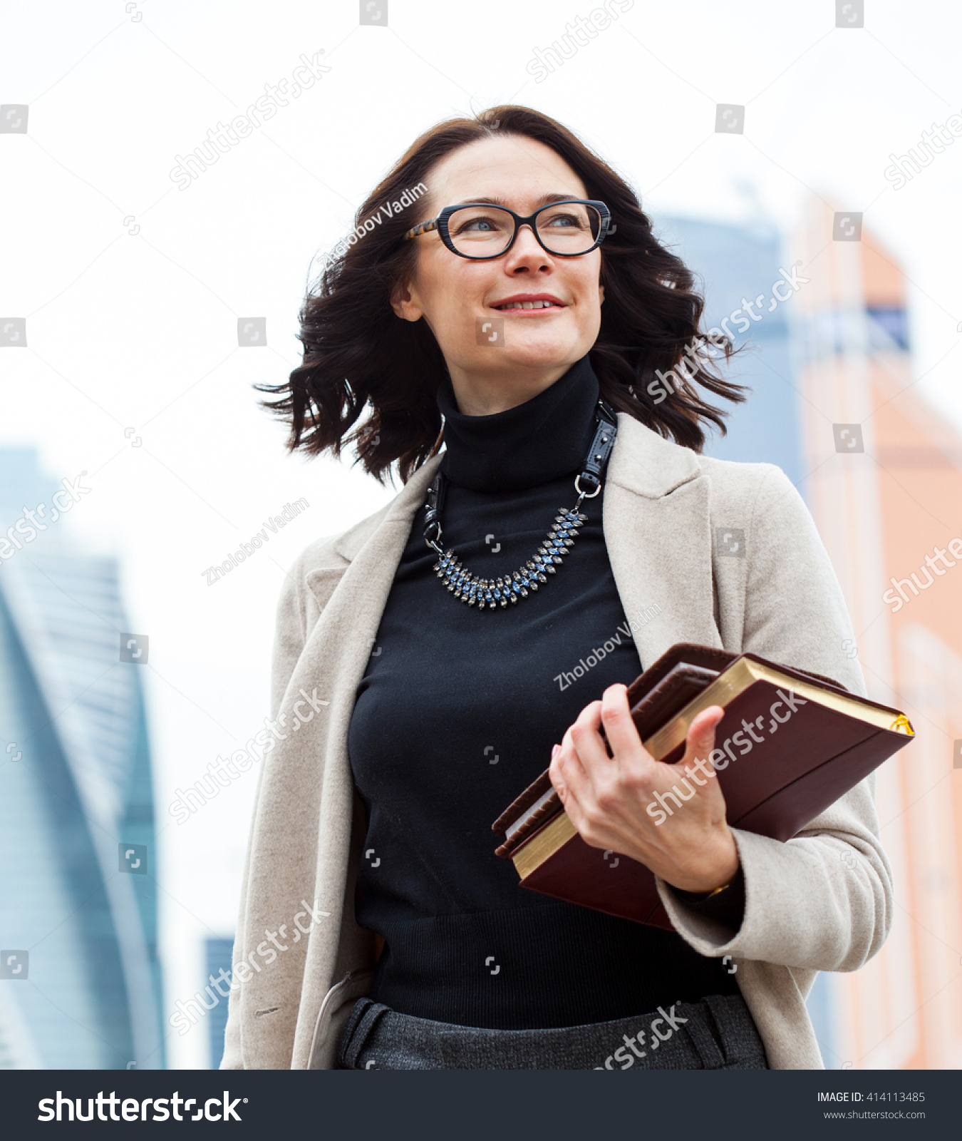smiling middle-aged woman with glasses on his face and with books in their hands on open air