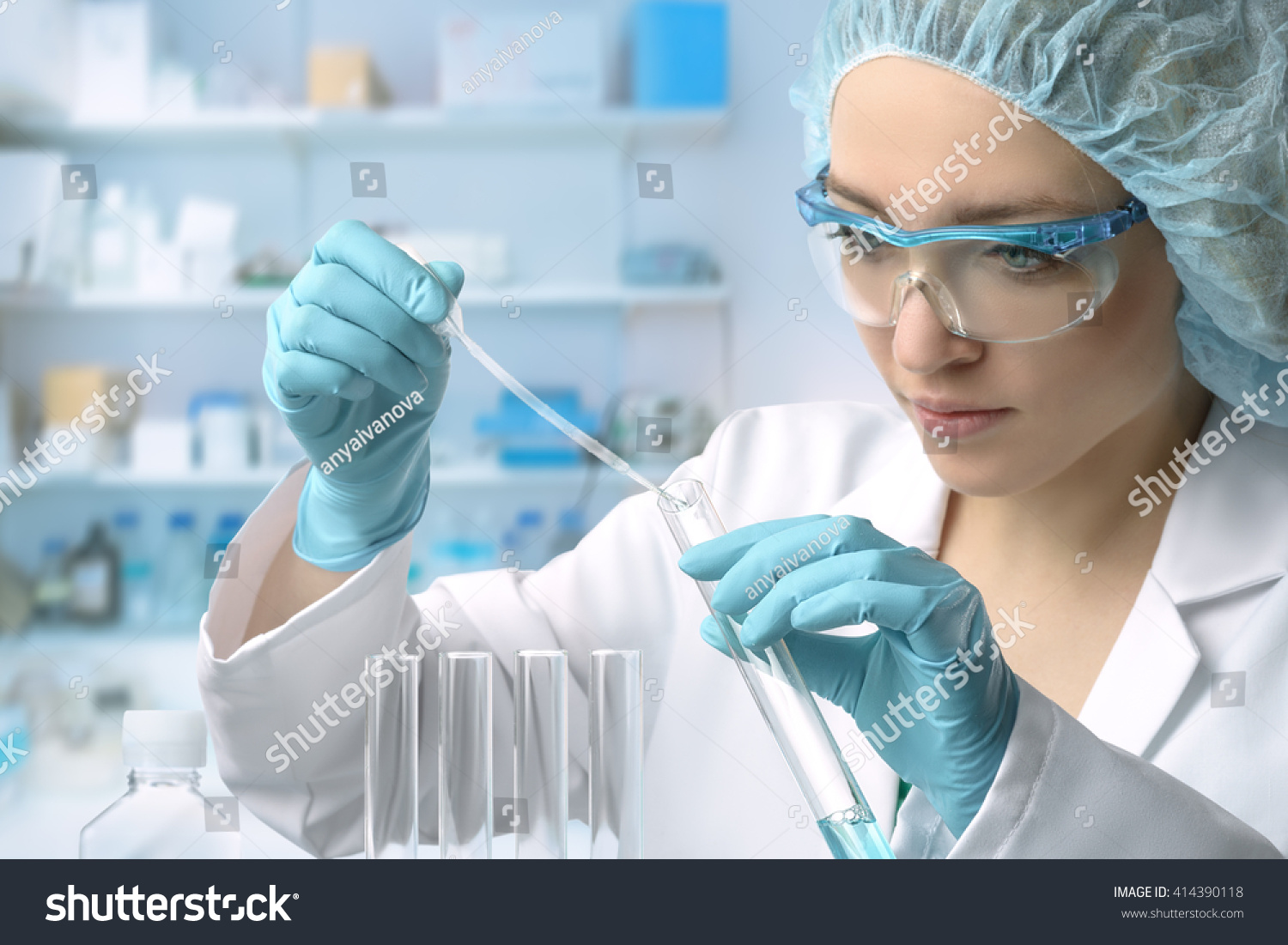 Young female tech or scientist loads liquid sample into test tube with plastic pipette. Shallow DOF, focus on the hand with the tube. #414390118