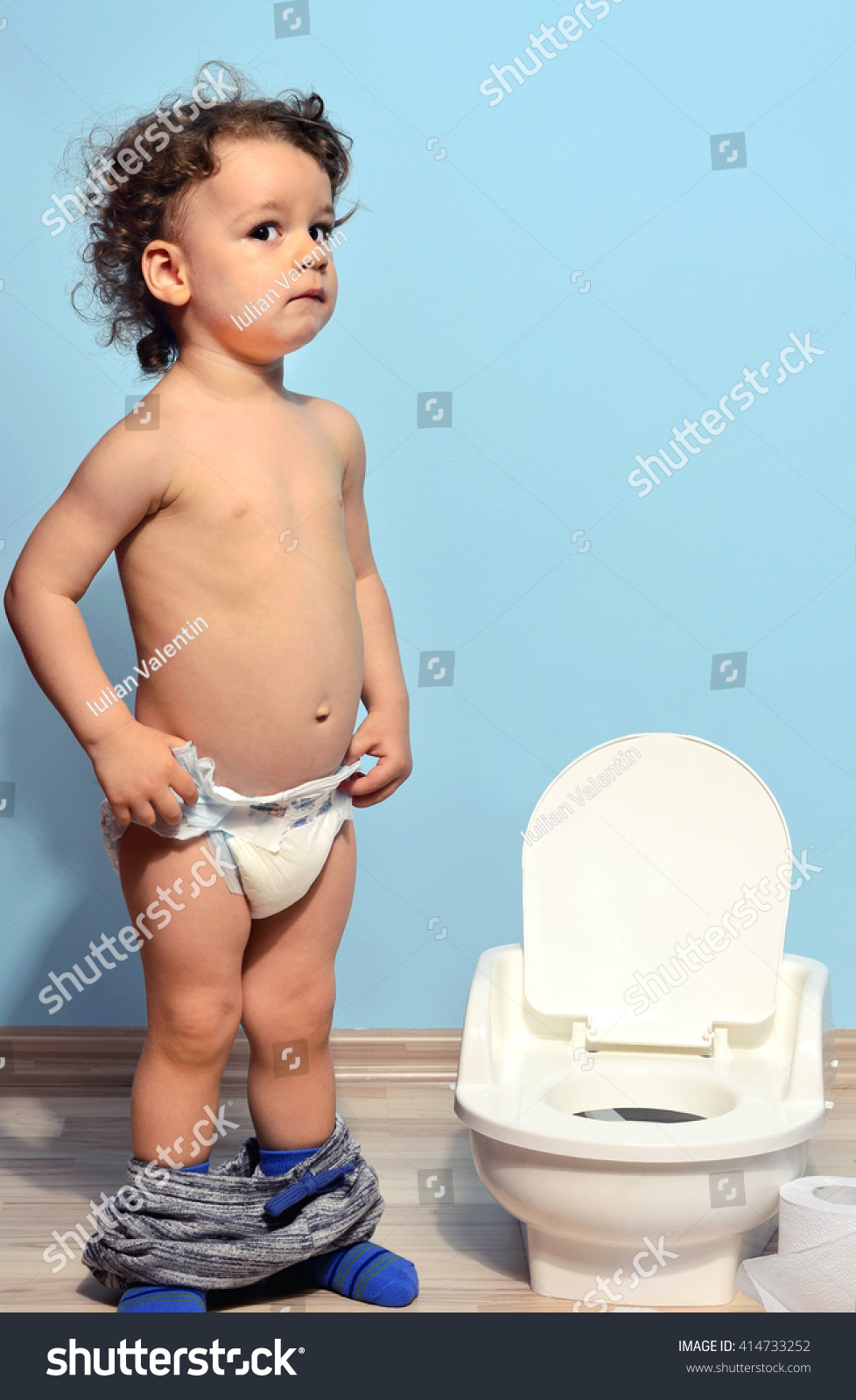 Toddler afraid to sit on the potty. Cute kid potty training for pee and poo