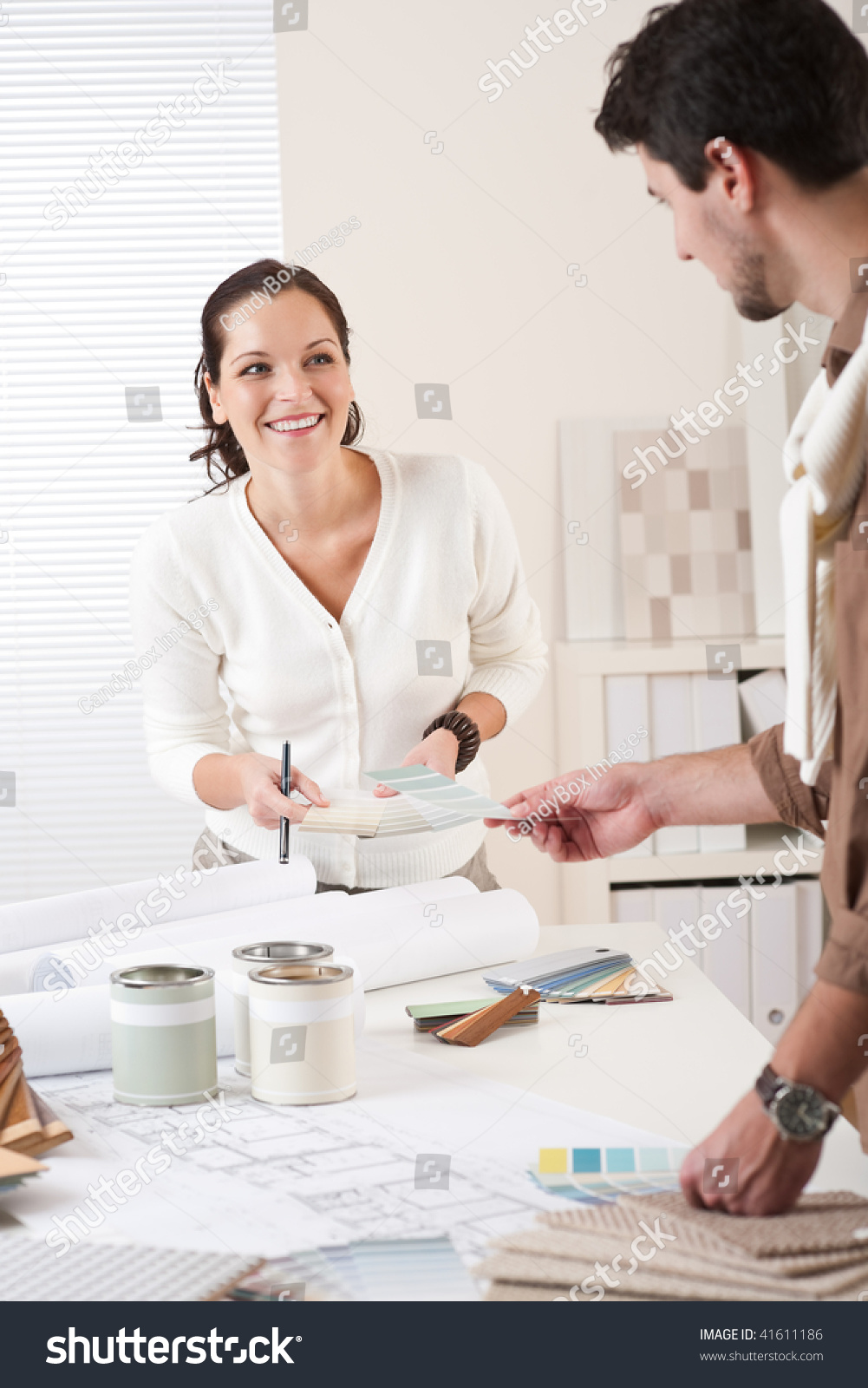 Two interior designer working at office with color swatch and can of paint stock photo 41611186 for Where can you work as an interior designer