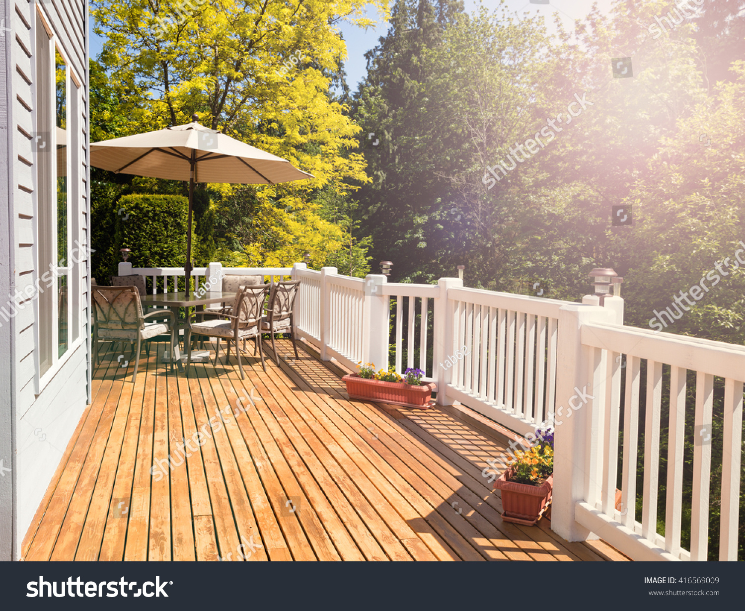 Afternoon bright daylight on outdoor home cedar deck with furniture and open umbrella. Light effect applied to image. Horizontal layout.  #416569009