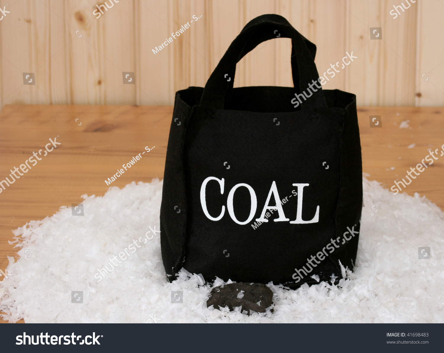 Small bag of coal in fake snow with a wooden background