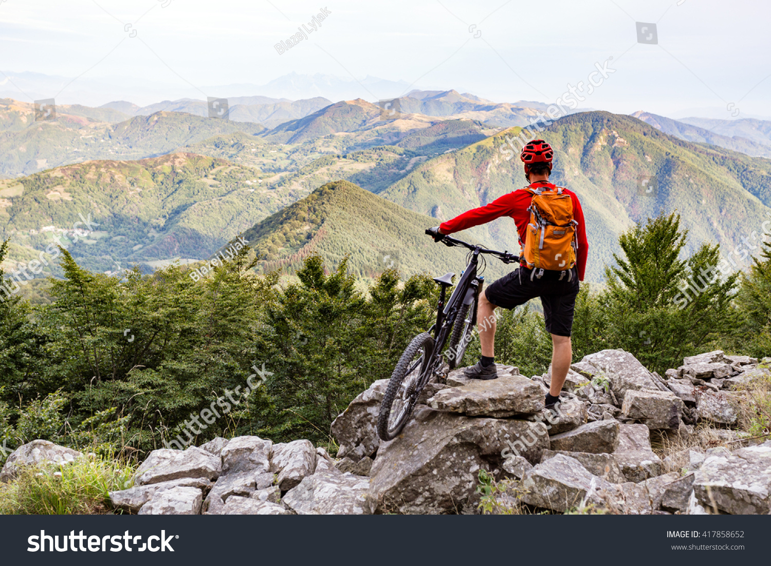 Mountain biker looking at view on bike trail in autumn mountains Rider cycling on rocky single track Sport fitness motivation and adventure inspiration
