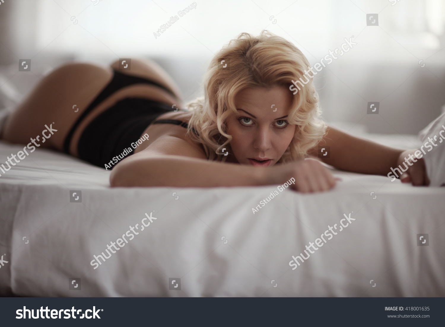 The lying on bed showing ass