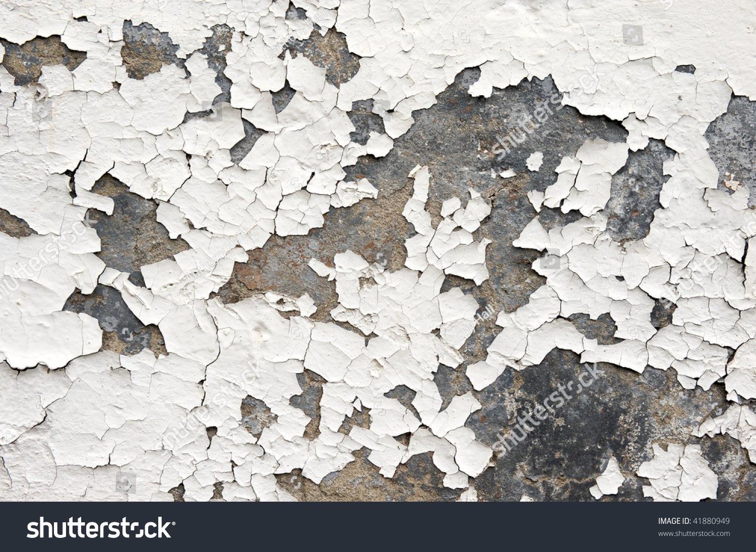 White Paint On An Exterior Wall Cracked And Flaking To Reveal Old Concrete Beneath Stock Photo