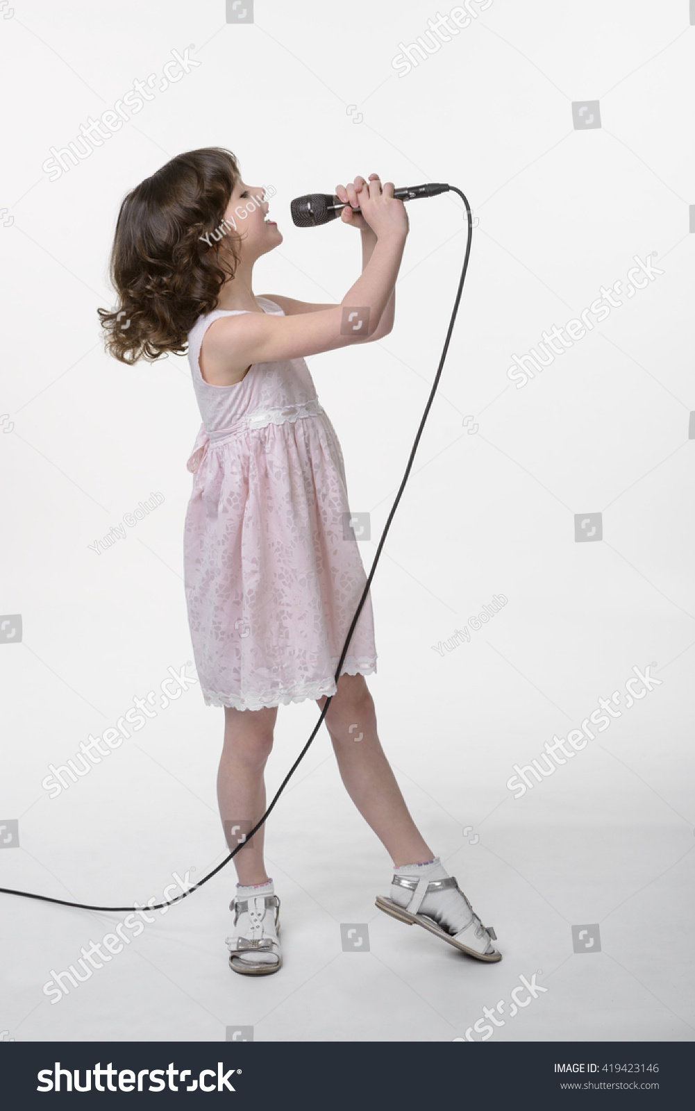 Young girl is recording her song in the studio Singing little cutie holds black microphone in her hands on the same level with her opened mouth Face in profile White background in the studio