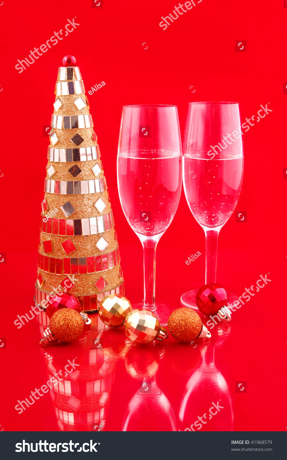 Artificial yellow christmas tree and champagne on red for Red and yellow christmas tree