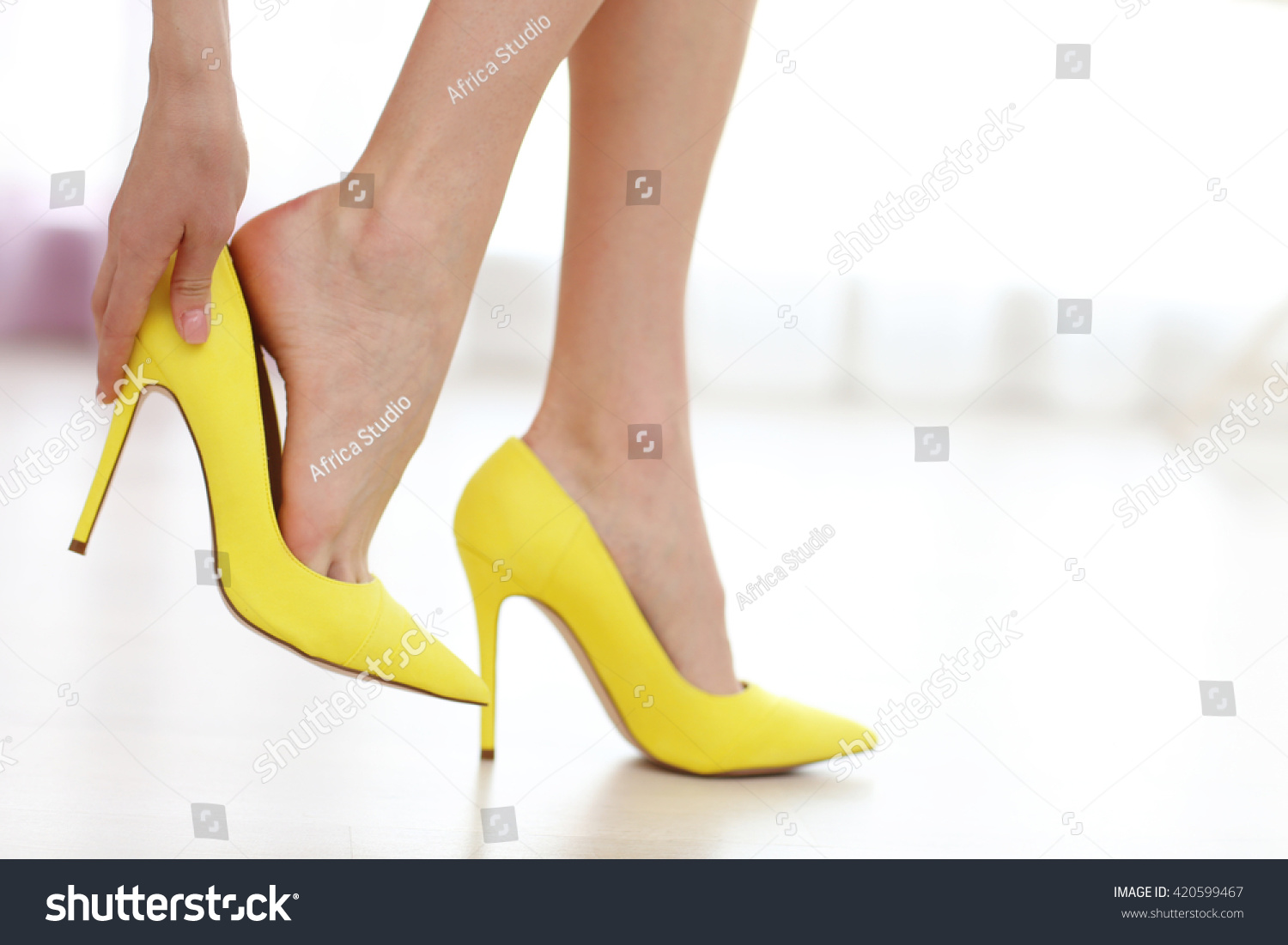 Woman taking off yellow high heels shoes. #420599467