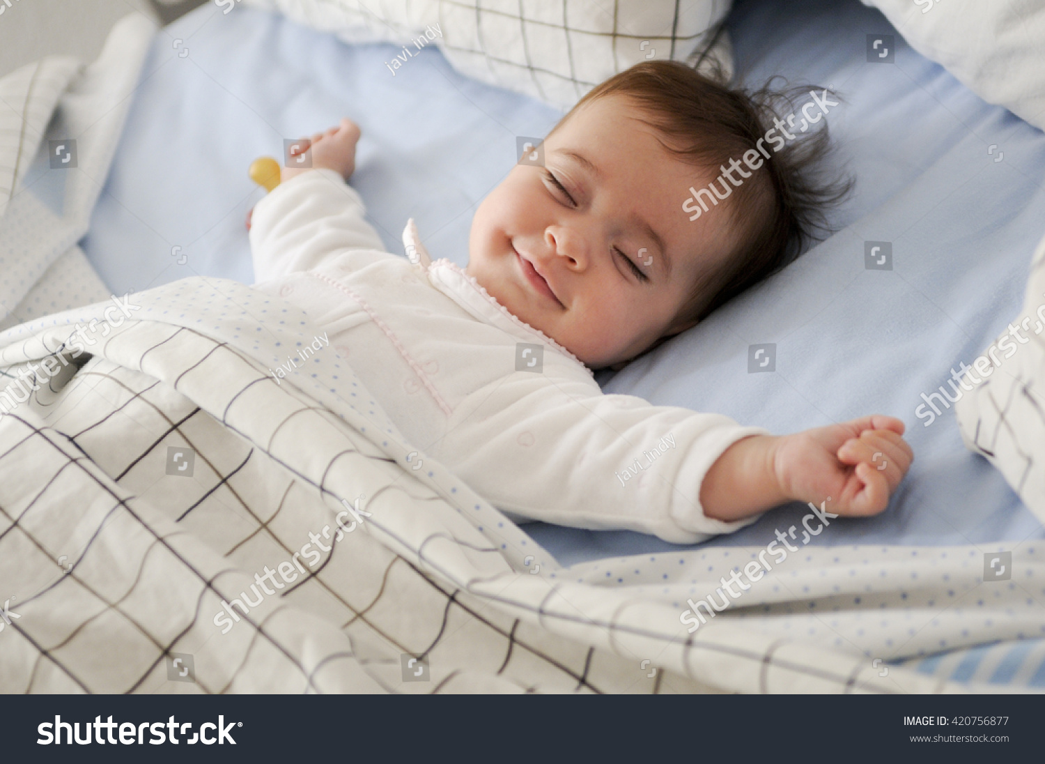 Smiling baby girl lying on a bed sleeping on blue sheets #420756877