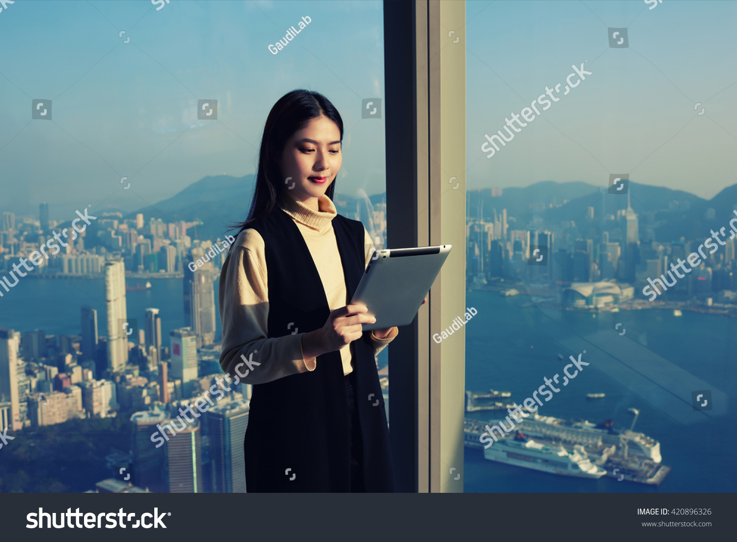 young chinese successful w ceo reading stock photo  young chinese successful w ceo is reading financial news in internet via portable digital tablet