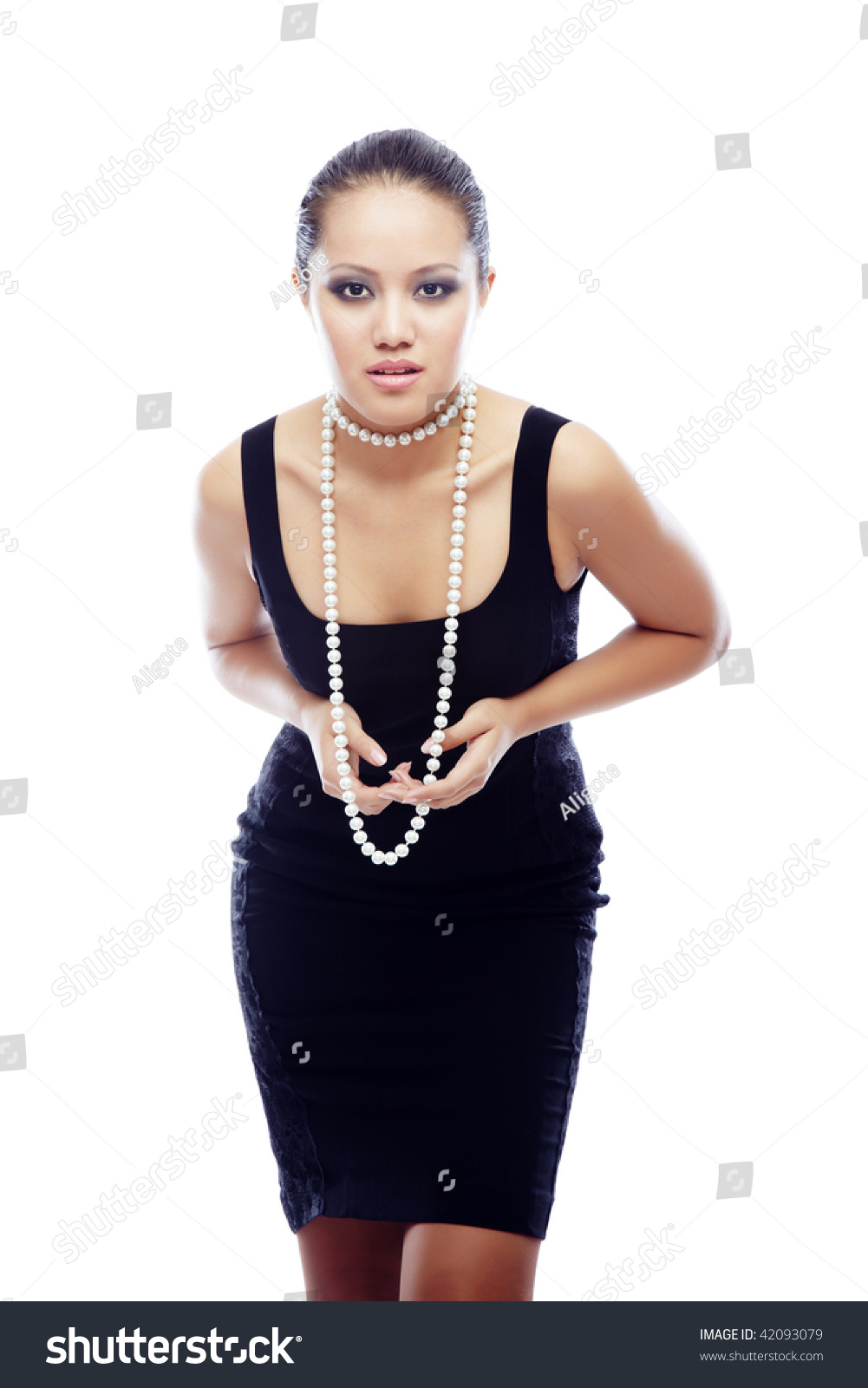 4c597a76950 Elegant Asian lady in the black dress with pearl necklace on a white  background